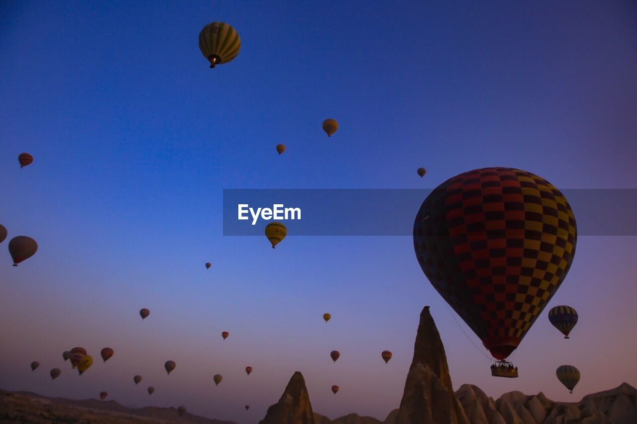 air vehicle, hot air balloon, flying, sky, balloon, mid-air, transportation, low angle view, ballooning festival, nature, mode of transportation, celebration, no people, adventure, clear sky, moving up, travel, outdoors, multi colored, tourism, festival