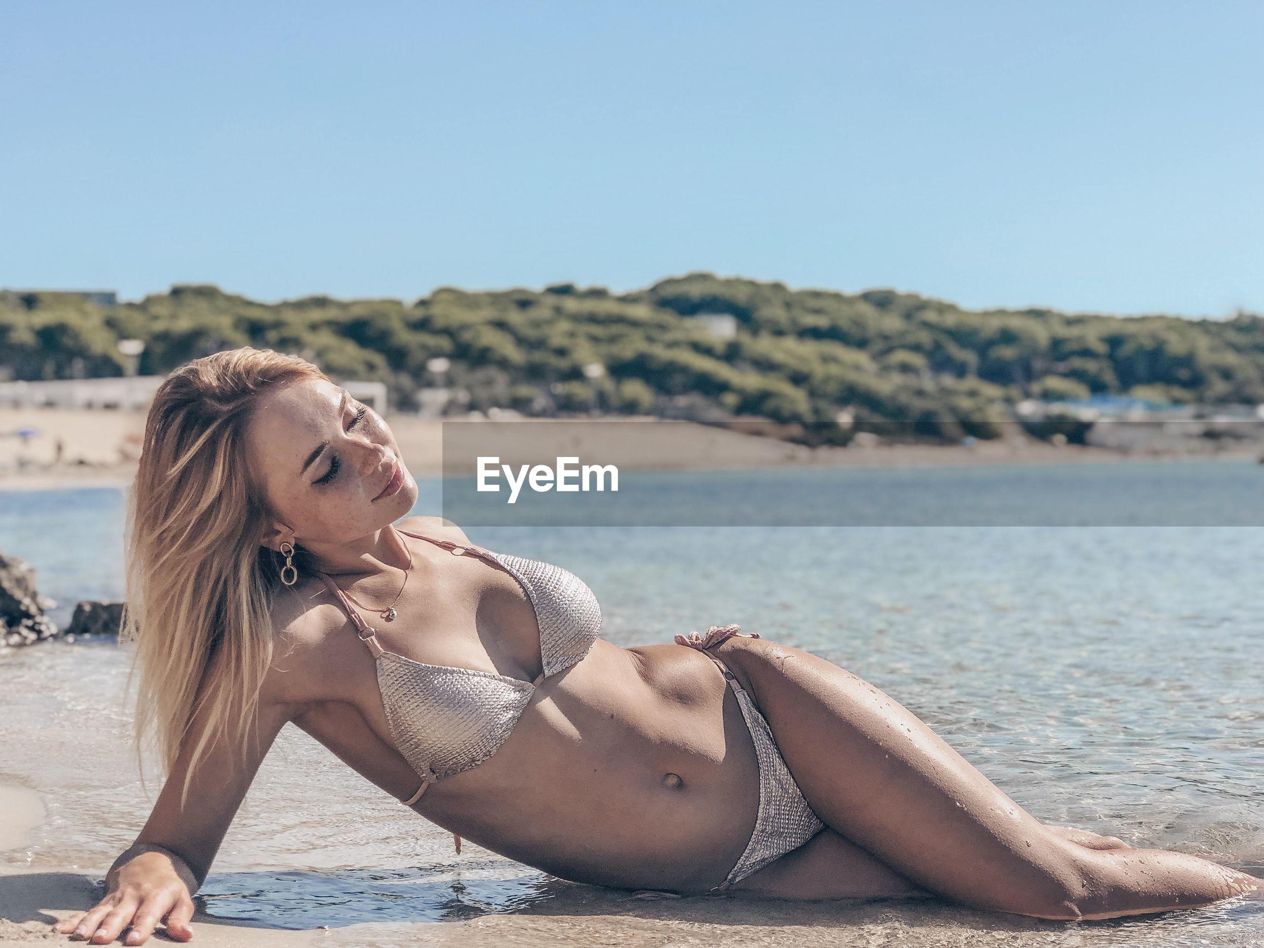 Young woman in bikini lying at beach against sky