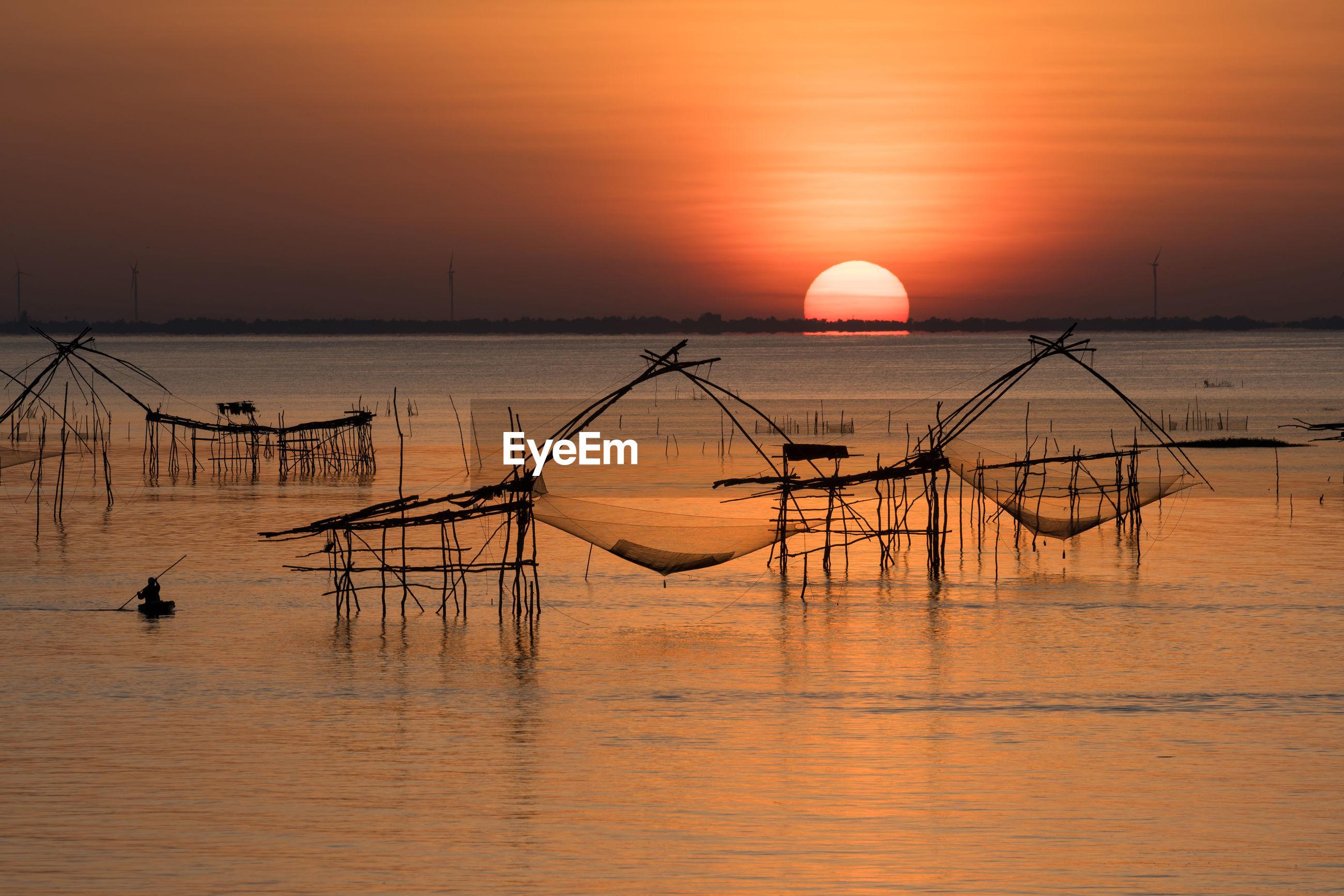 Silhouette fishing nets in sea against orange sky