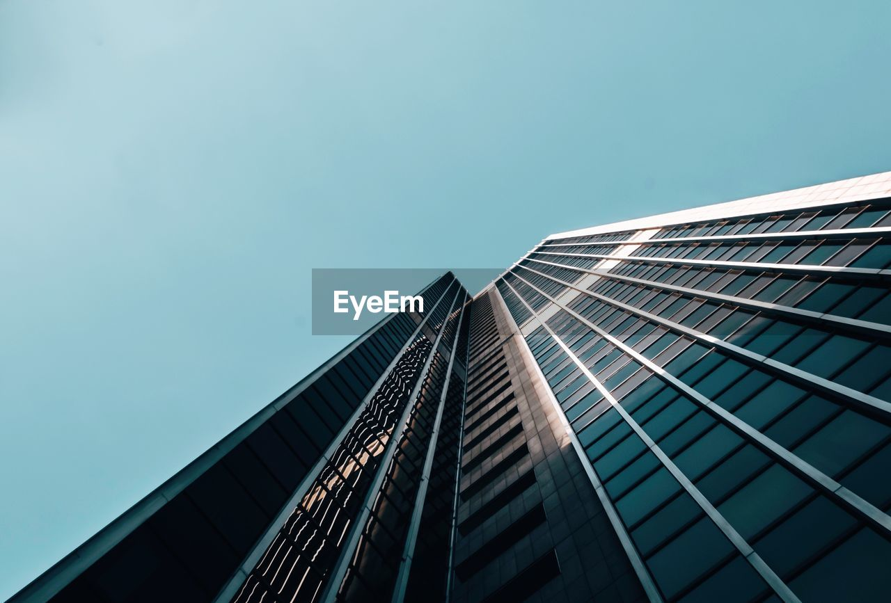 built structure, architecture, building exterior, low angle view, office building exterior, city, building, sky, modern, office, tall - high, skyscraper, clear sky, blue, copy space, nature, no people, glass - material, day, outdoors, directly below