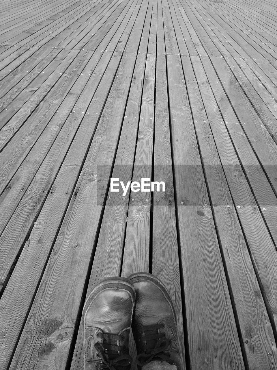 Low Section Of Person On Wooden Planks
