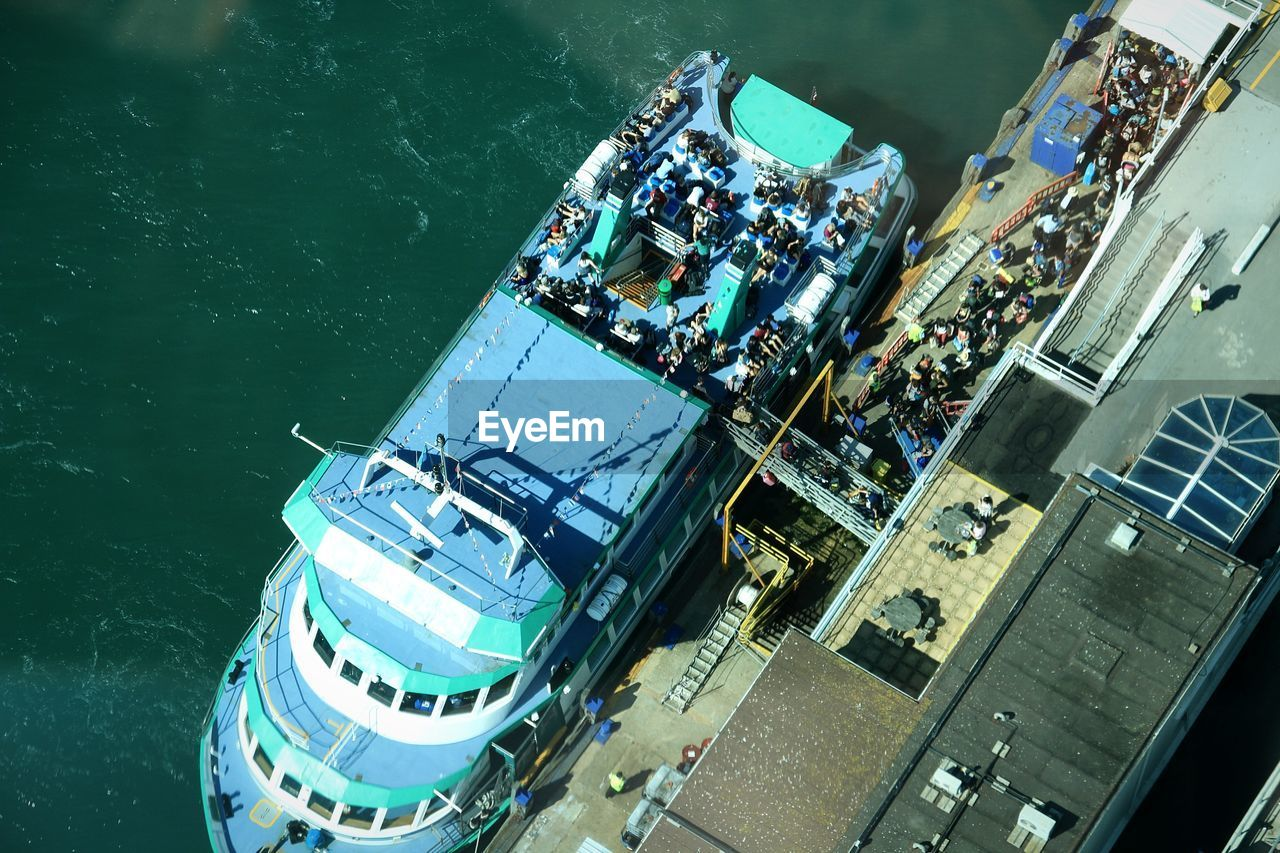 HIGH ANGLE VIEW OF PEOPLE ON SHIP IN SEA