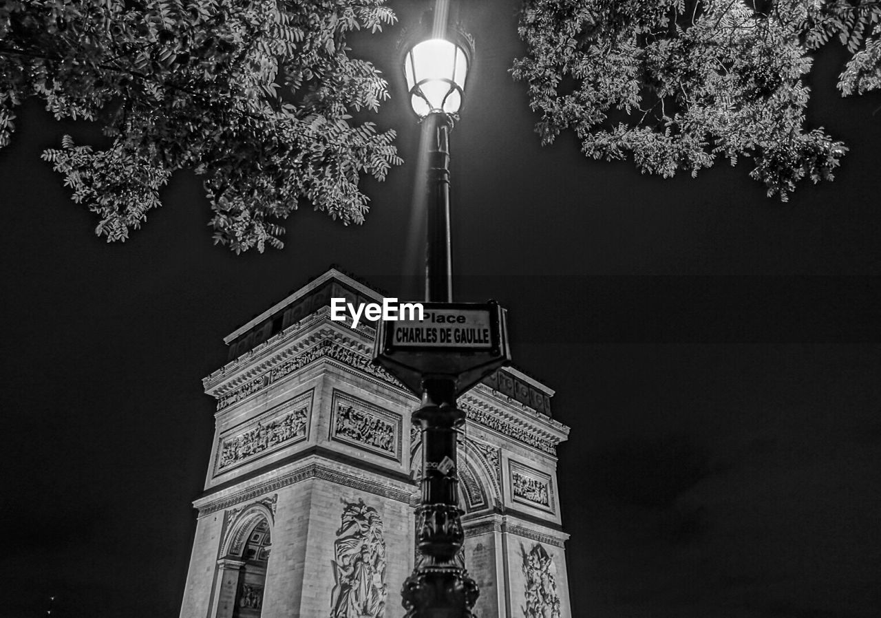 illuminated, tree, lighting equipment, street light, night, architecture, low angle view, built structure, travel destinations, no people, outdoors, branch, building exterior, sky, city, nature