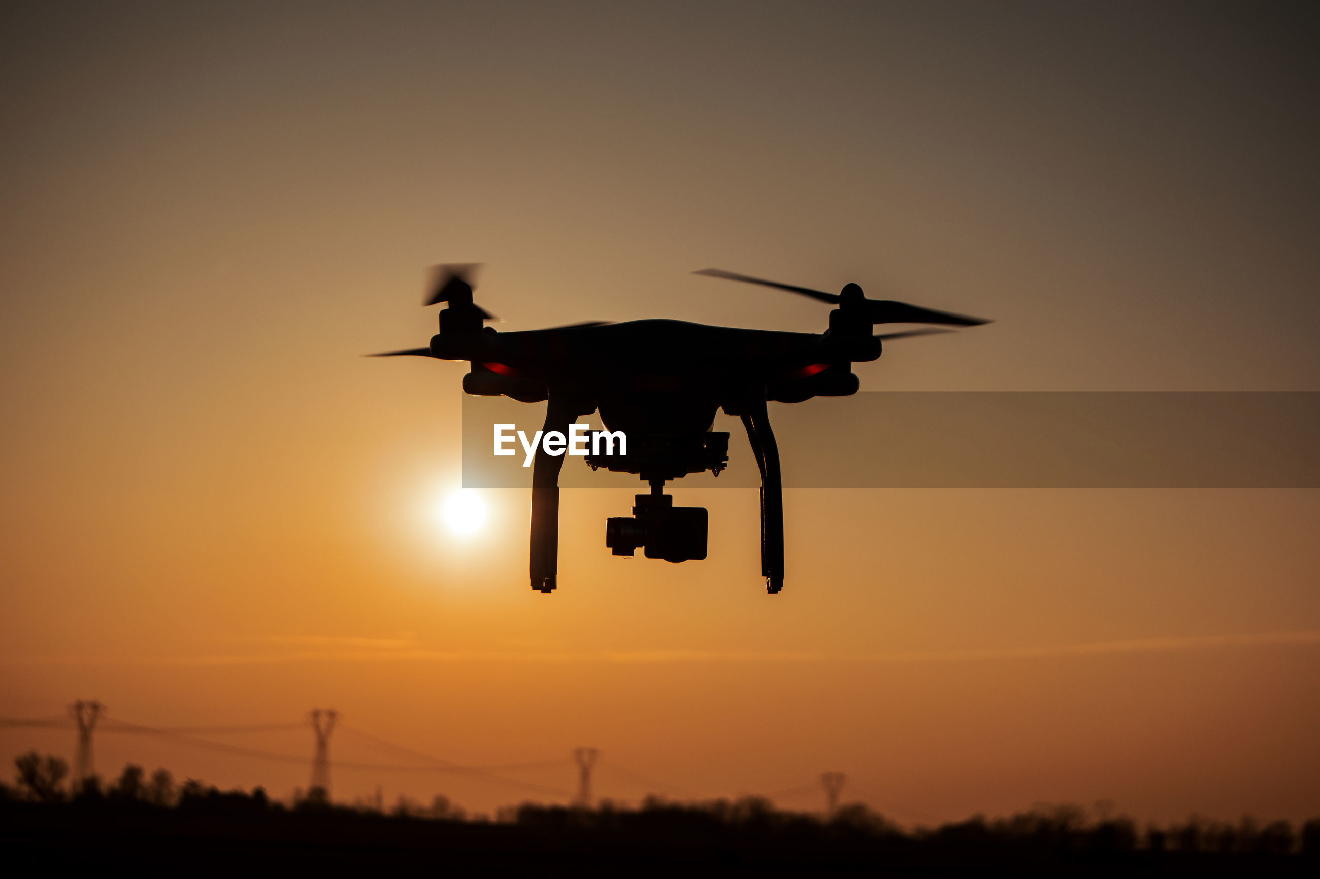 Silhouette drone against sky during sunset