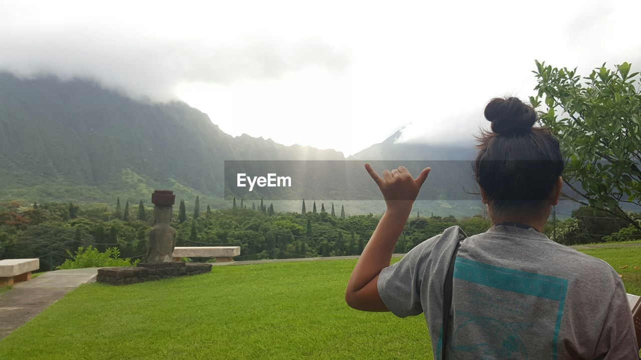 Rear view of girl gesturing against mountains on sunny day