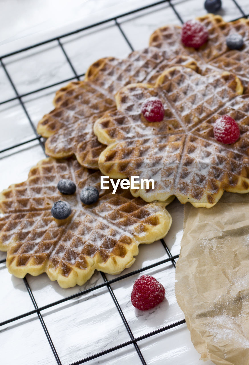 food, food and drink, freshness, sweet food, ready-to-eat, dessert, fruit, indulgence, sweet, still life, indoors, temptation, baked, close-up, unhealthy eating, berry fruit, cake, cooling rack, no people, waffle, baked pastry item, snack, powdered sugar, tart - dessert, breakfast, baking sheet