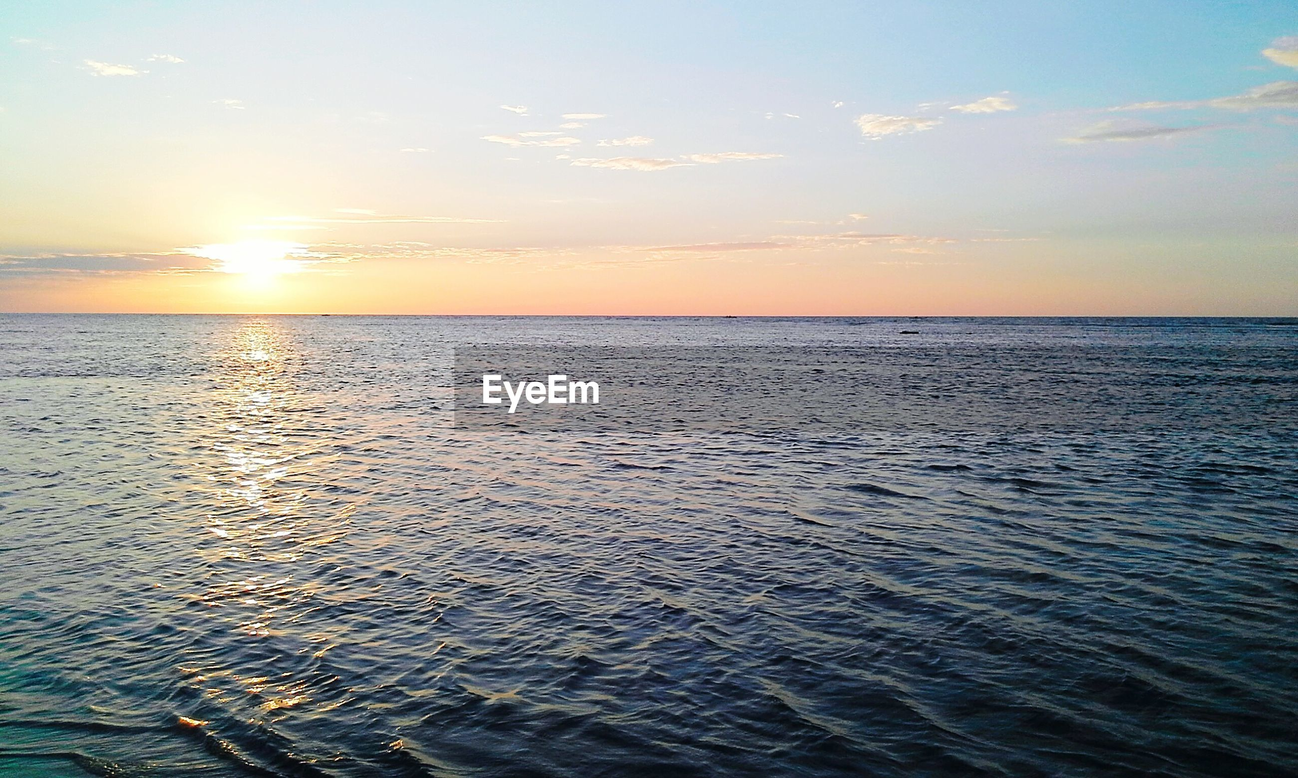 sea, water, horizon over water, sunset, tranquil scene, scenics, beauty in nature, sun, tranquility, sky, rippled, idyllic, nature, reflection, waterfront, seascape, orange color, sunlight, beach, cloud - sky