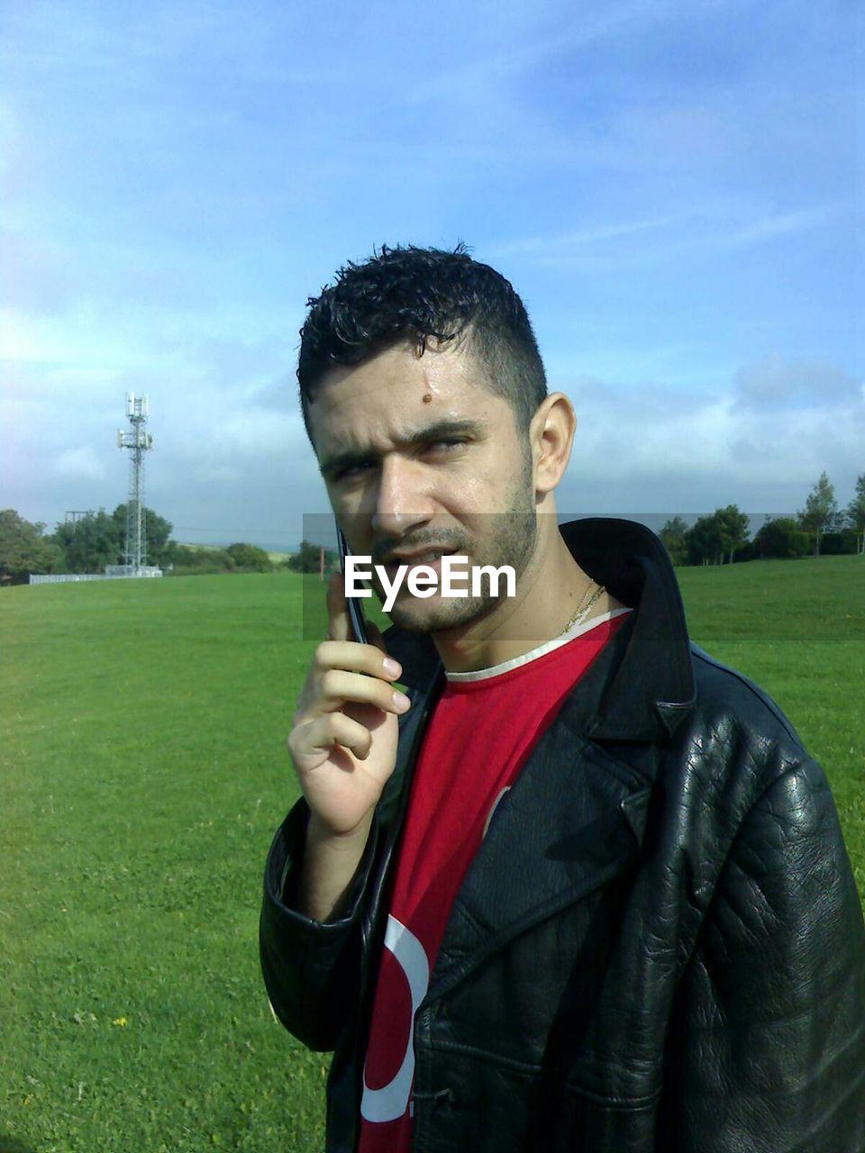 Man listening on mobile phone on grass in park against sky