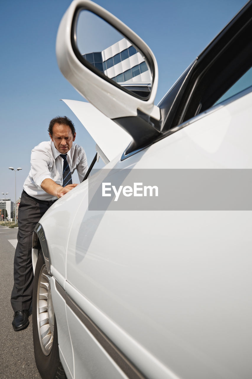MAN STANDING ON A CAR