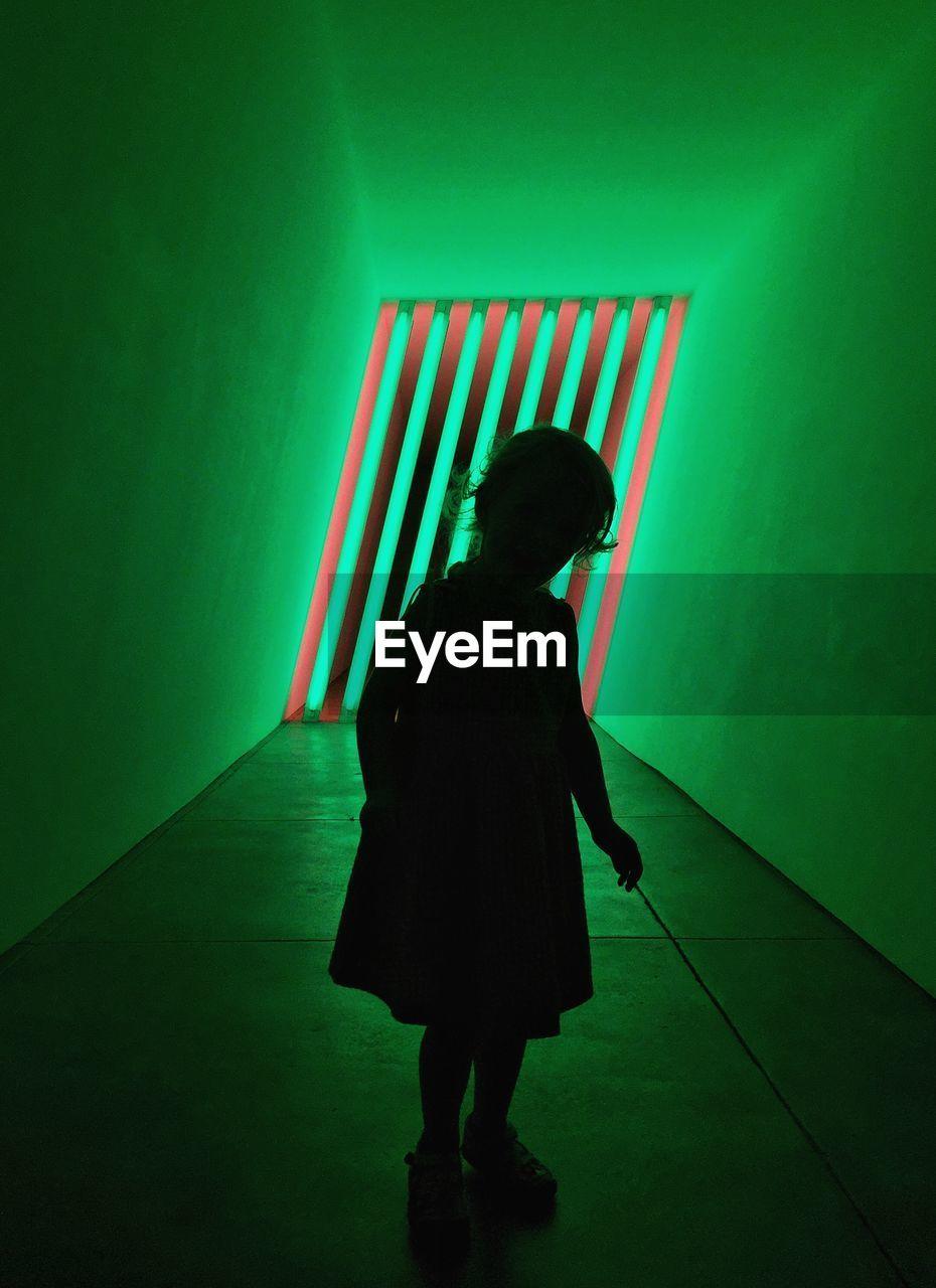 Girl Standing On Illuminated Corridor