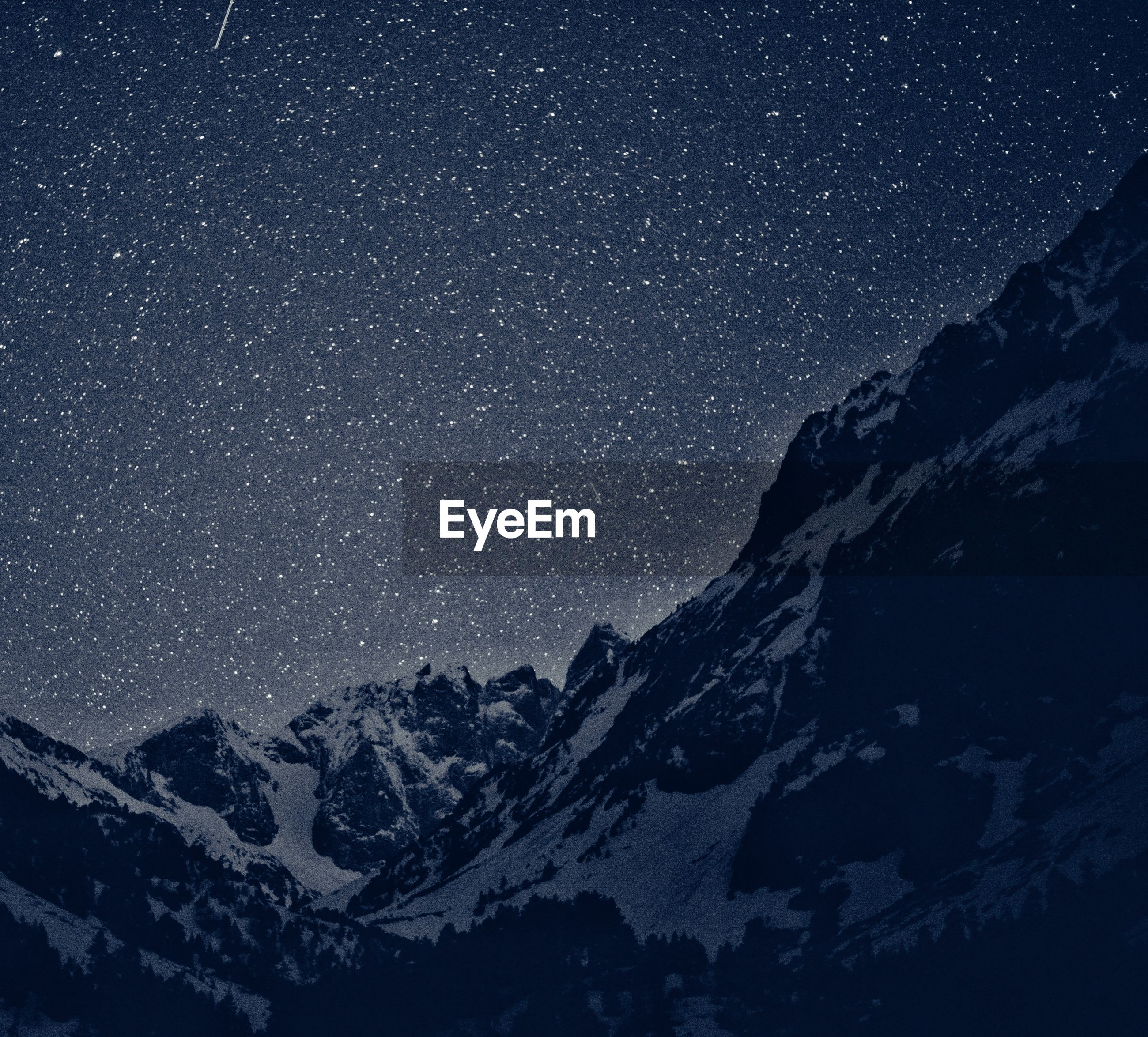 Scenic view of snowcapped mountain against star field at night