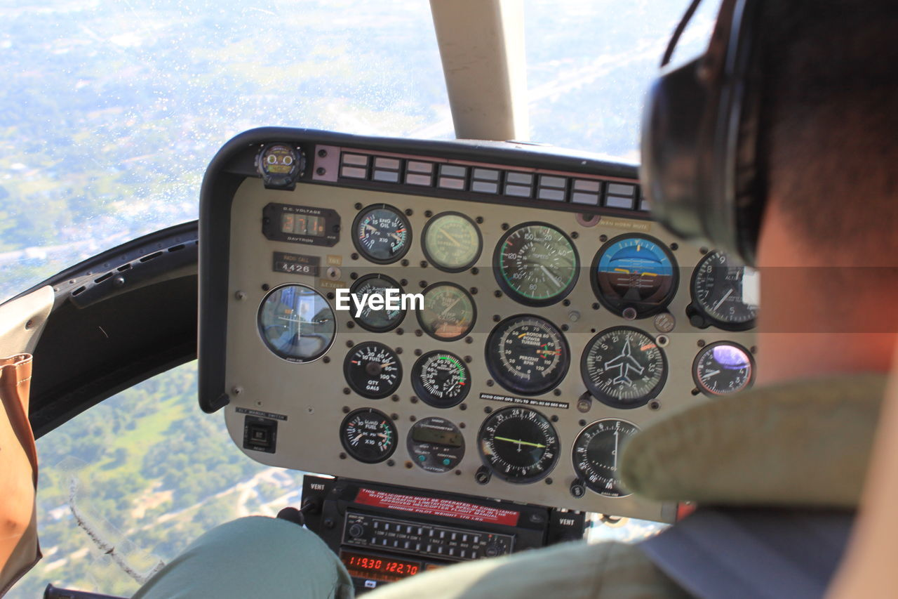 airplane, cockpit, air vehicle, pilot, mode of transportation, vehicle interior, transportation, control, travel, men, flying, glass - material, rear view, two people, control panel, real people, piloting, technology, aerospace industry, day, outdoors, uniform, co-pilot, over the shoulder view