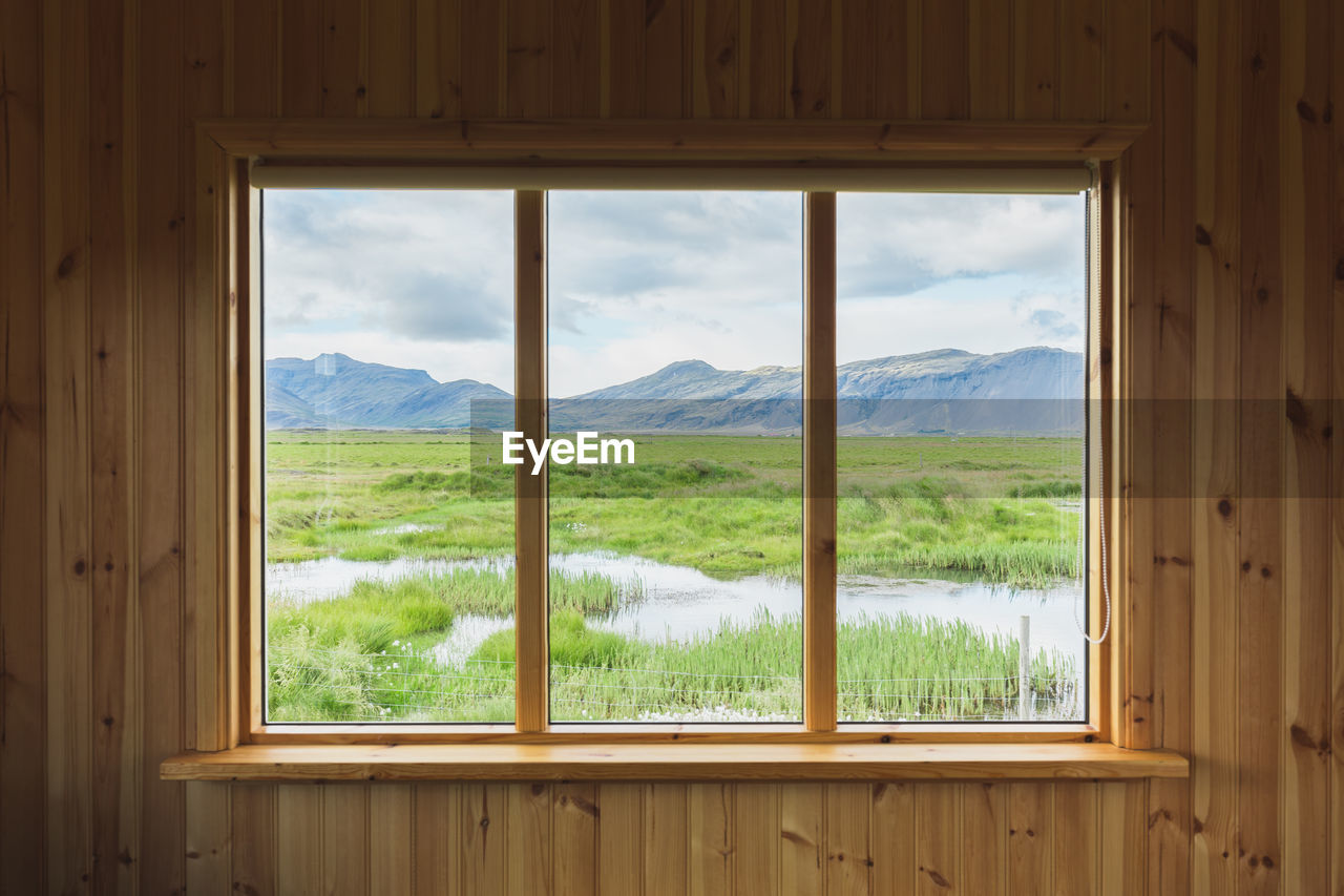 window, scenics - nature, mountain, beauty in nature, no people, mountain range, landscape, day, wood - material, nature, indoors, sky, environment, plant, cloud - sky, land, tranquil scene, transparent, tree, window frame