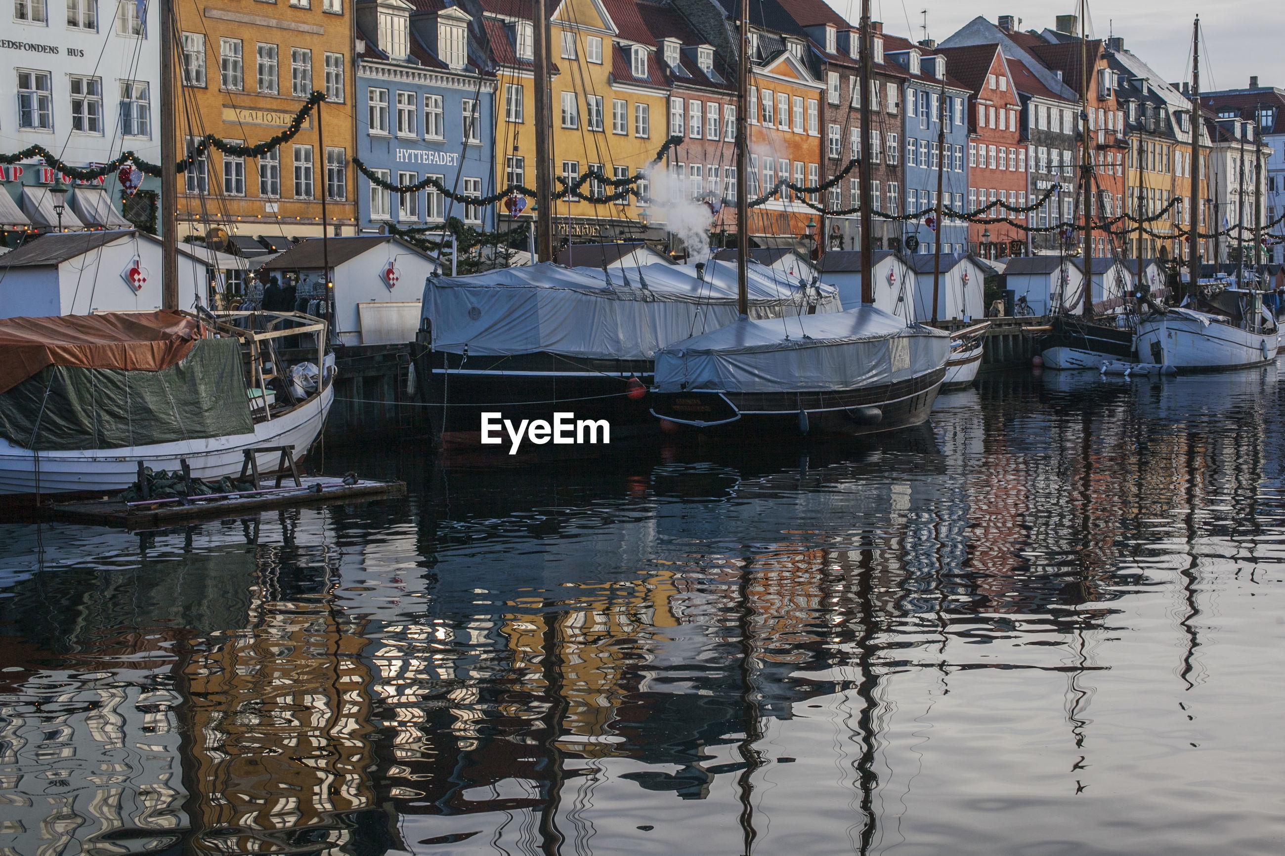 Boats moored in canal by buildings in city, copenhagen