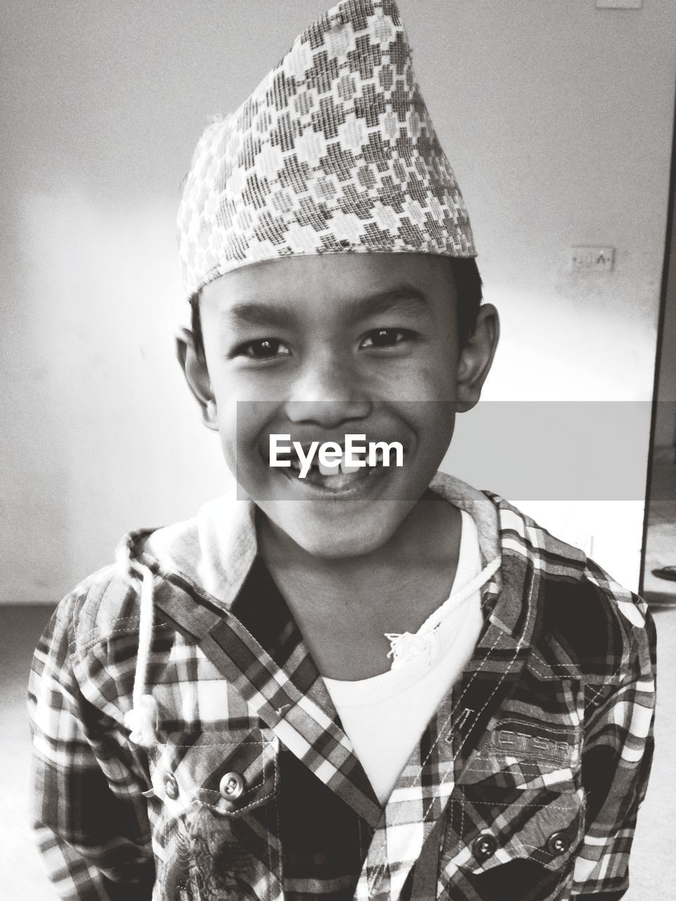 Portrait of smiling boy wearing topi at home