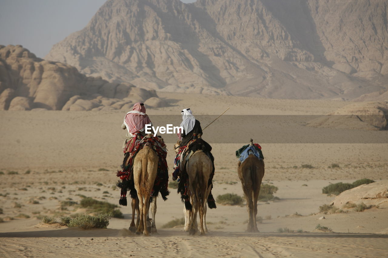 Rear View Of People Riding Camels On Desert Landscape Against Mountain