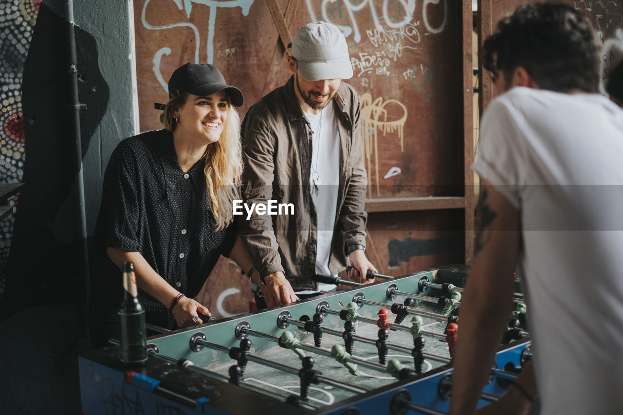 leisure activity, women, leisure games, young adult, young women, standing, game, real people, indoors, adult, clothing, people, hat, lifestyles, board game, waist up, arts culture and entertainment, playing, hairstyle