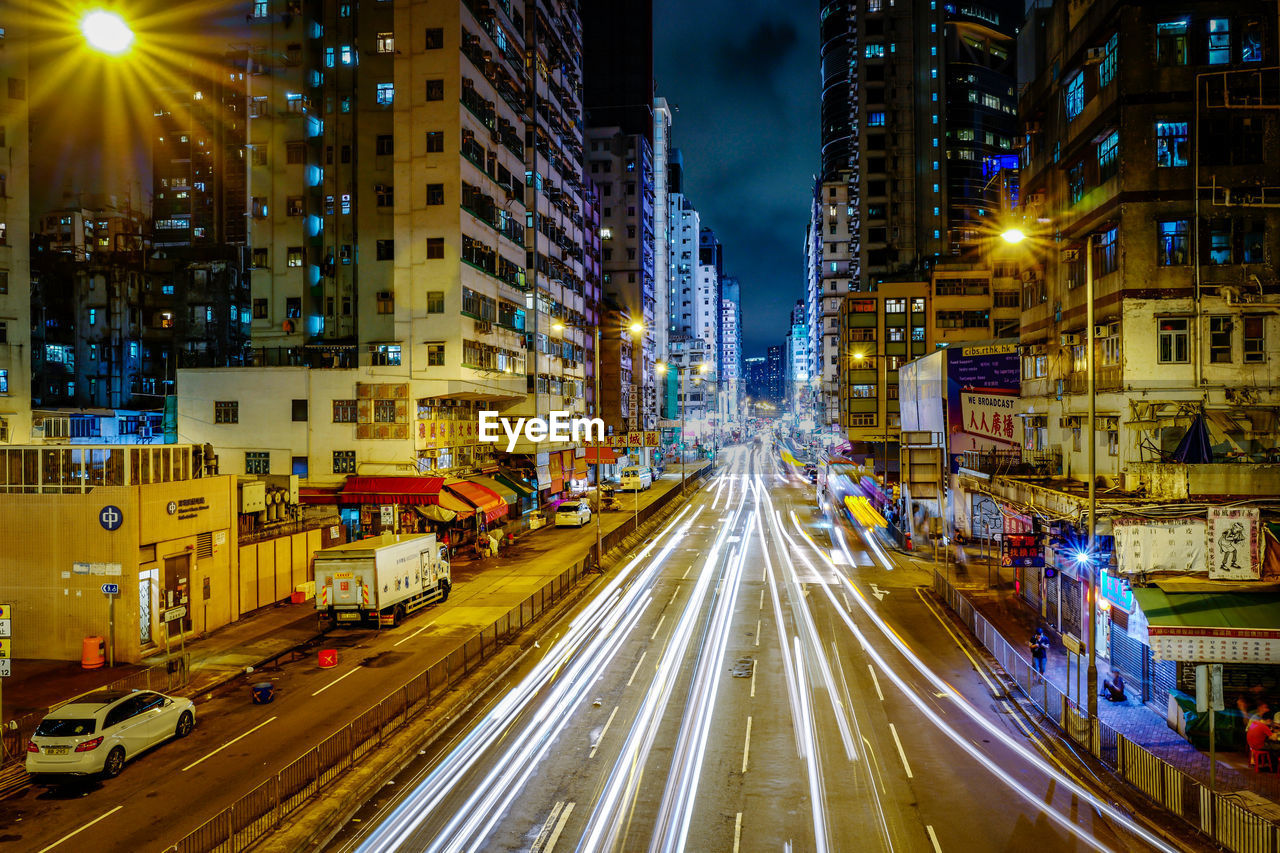 city, building exterior, architecture, illuminated, built structure, night, street, transportation, motion, road, long exposure, speed, light trail, blurred motion, building, city life, mode of transportation, traffic, no people, high angle view, cityscape, city street, office building exterior, outdoors, skyscraper, light, busy