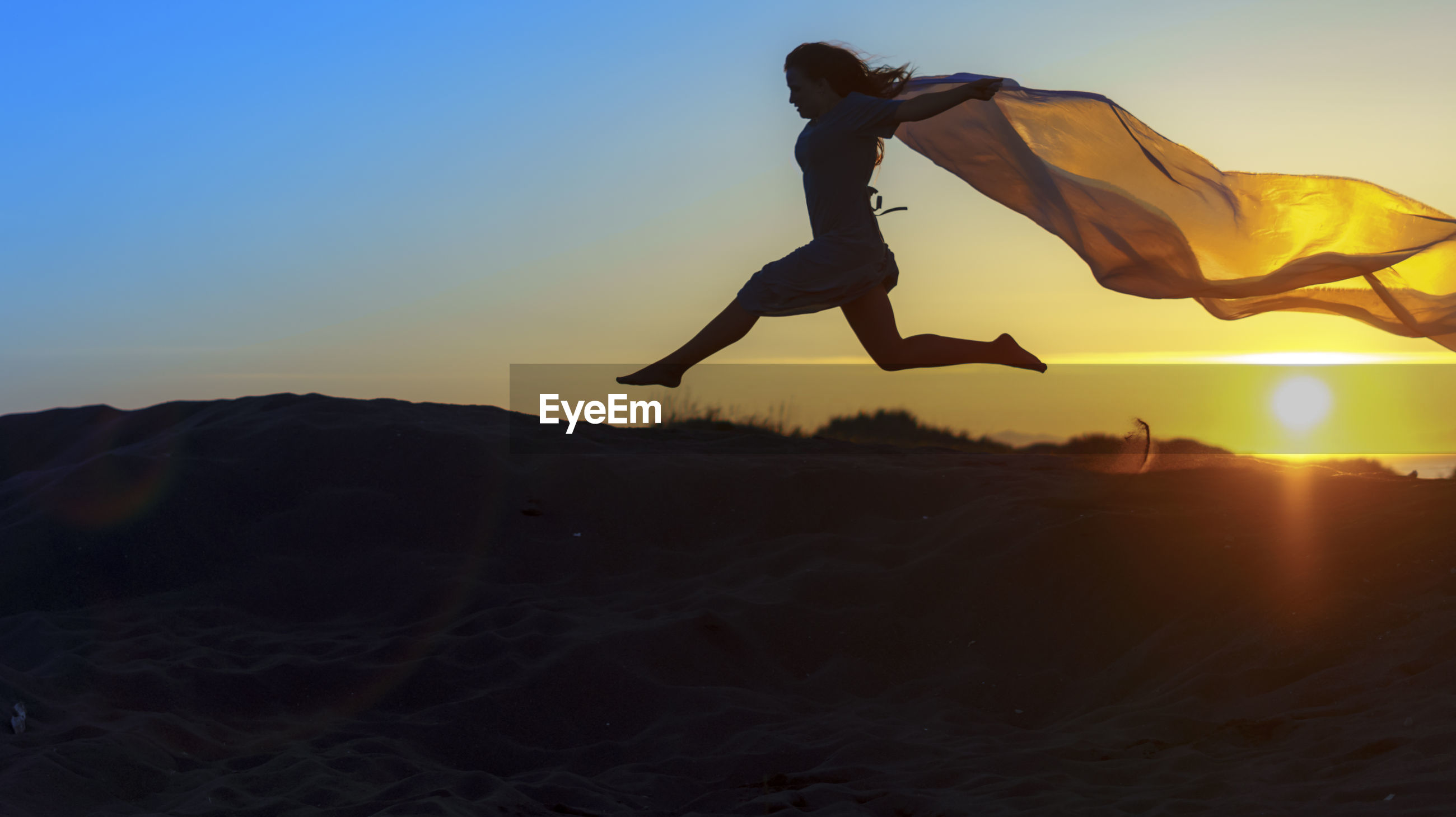 View of woman jumping at sunset