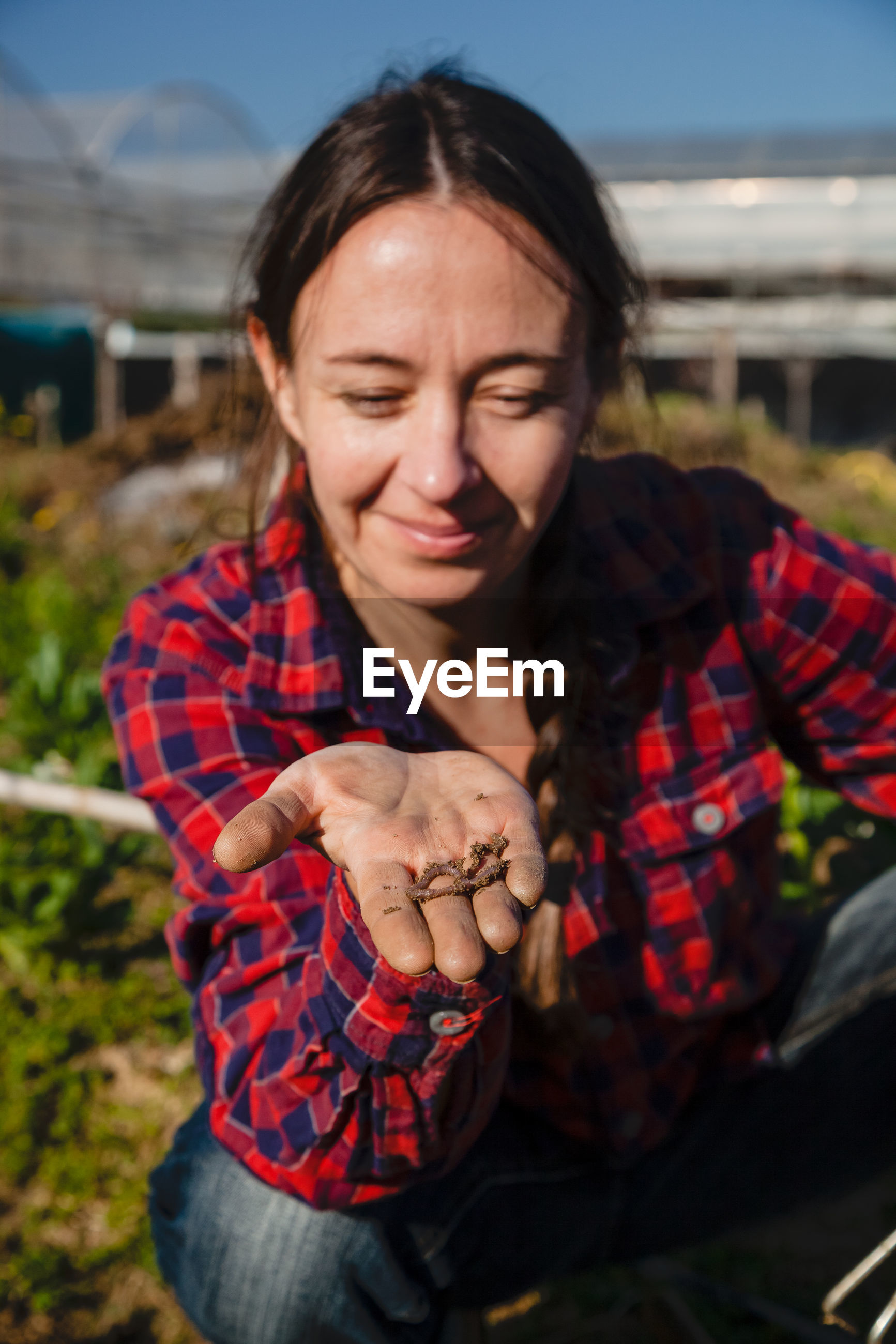 Smiling woman holding earthworm while gardening