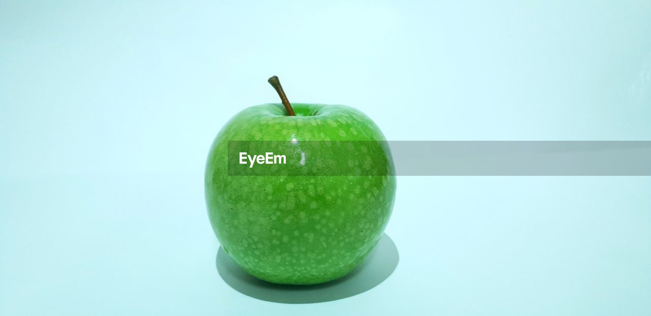 fruit, green color, studio shot, healthy eating, food, food and drink, apple - fruit, freshness, indoors, still life, no people, wellbeing, copy space, single object, close-up, colored background, cut out, granny smith apple, white background, apple, blue background