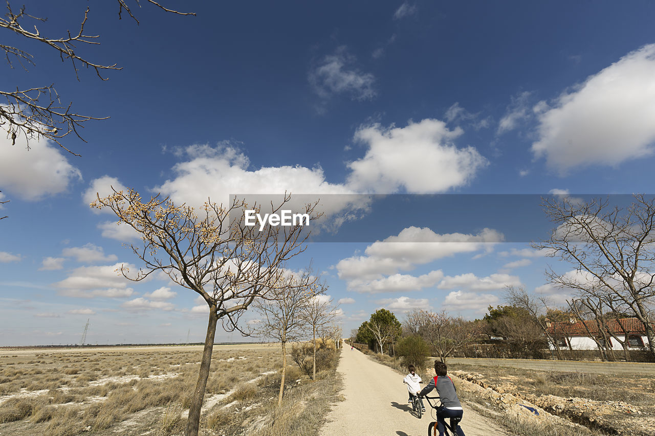 Rear View Of Siblings Riding Bicycles By Landscape On Road