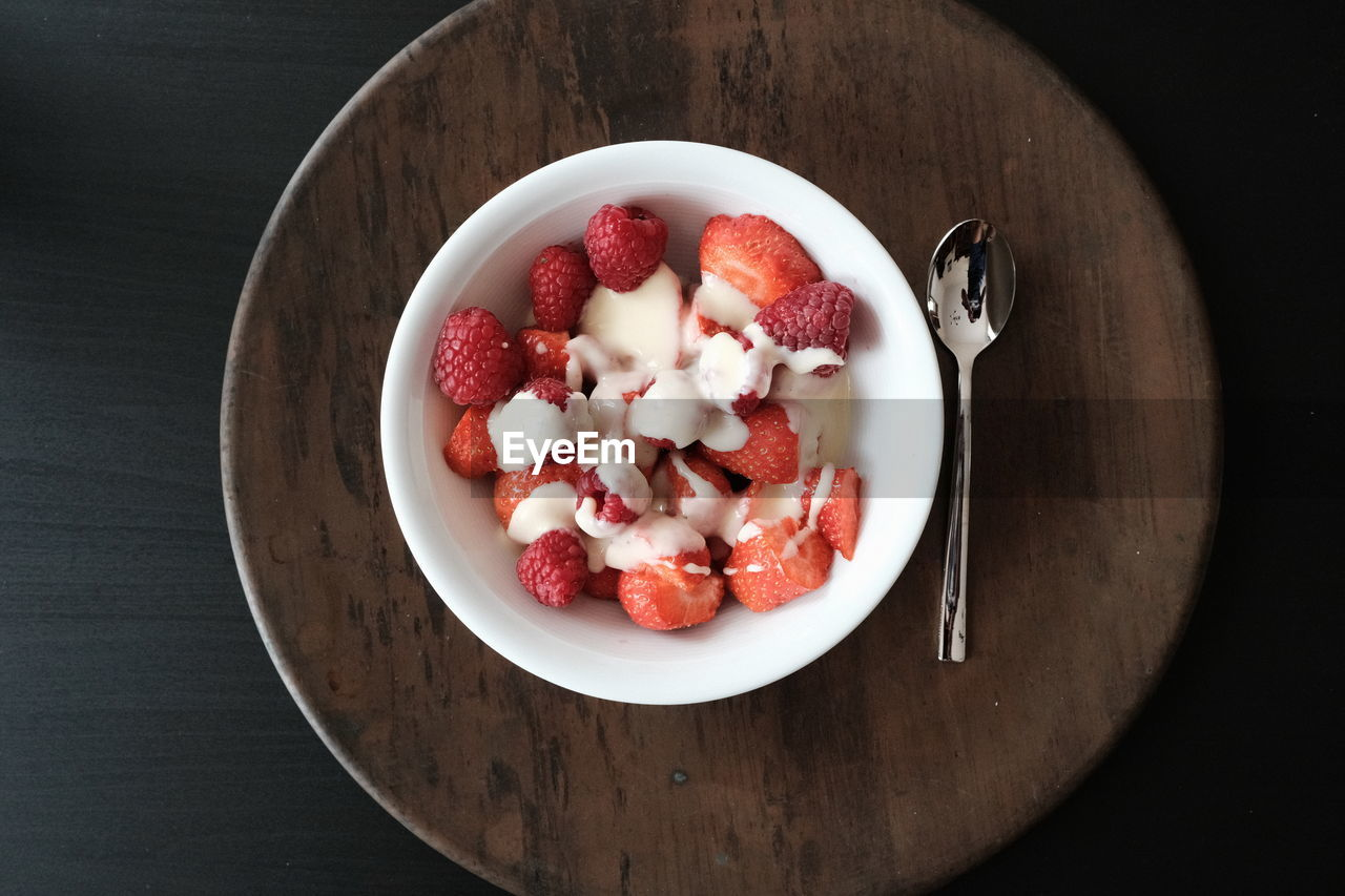 food and drink, fruit, freshness, food, wellbeing, healthy eating, bowl, table, directly above, wood - material, still life, indoors, high angle view, berry fruit, no people, ready-to-eat, red, strawberry, kitchen utensil, eating utensil, chopped, fruit salad