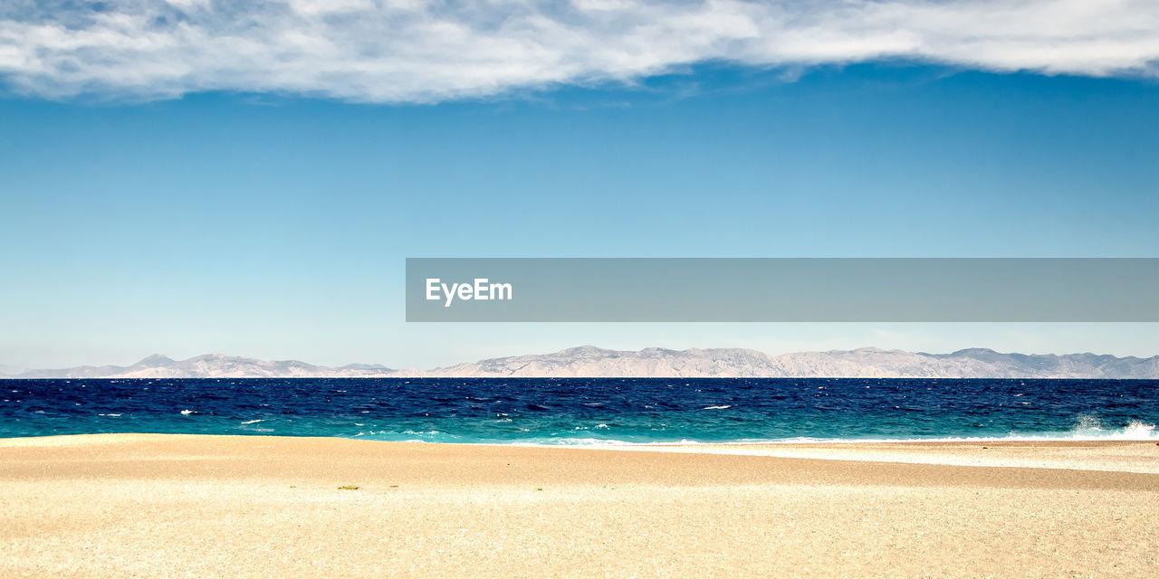 VIEW OF BEACH AGAINST BLUE SKY