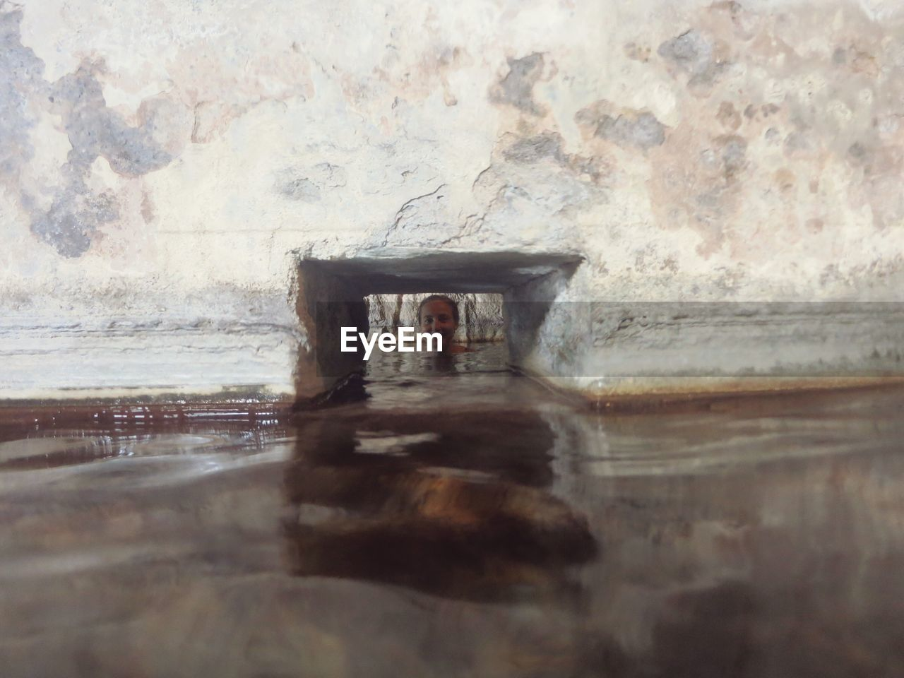 Portrait of woman seen through hole on wall in hot spring