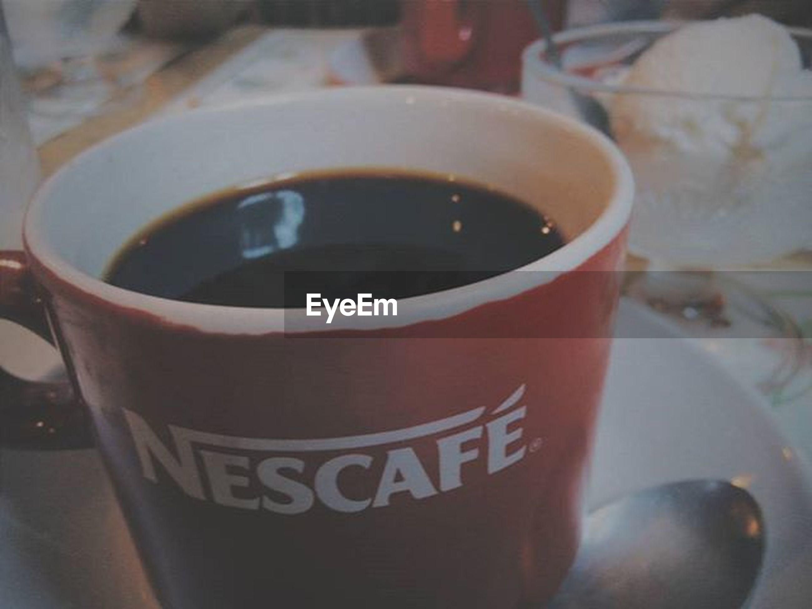 drink, food and drink, coffee cup, text, indoors, refreshment, close-up, western script, coffee - drink, communication, focus on foreground, freshness, still life, table, coffee, cup, saucer, frothy drink, red, selective focus