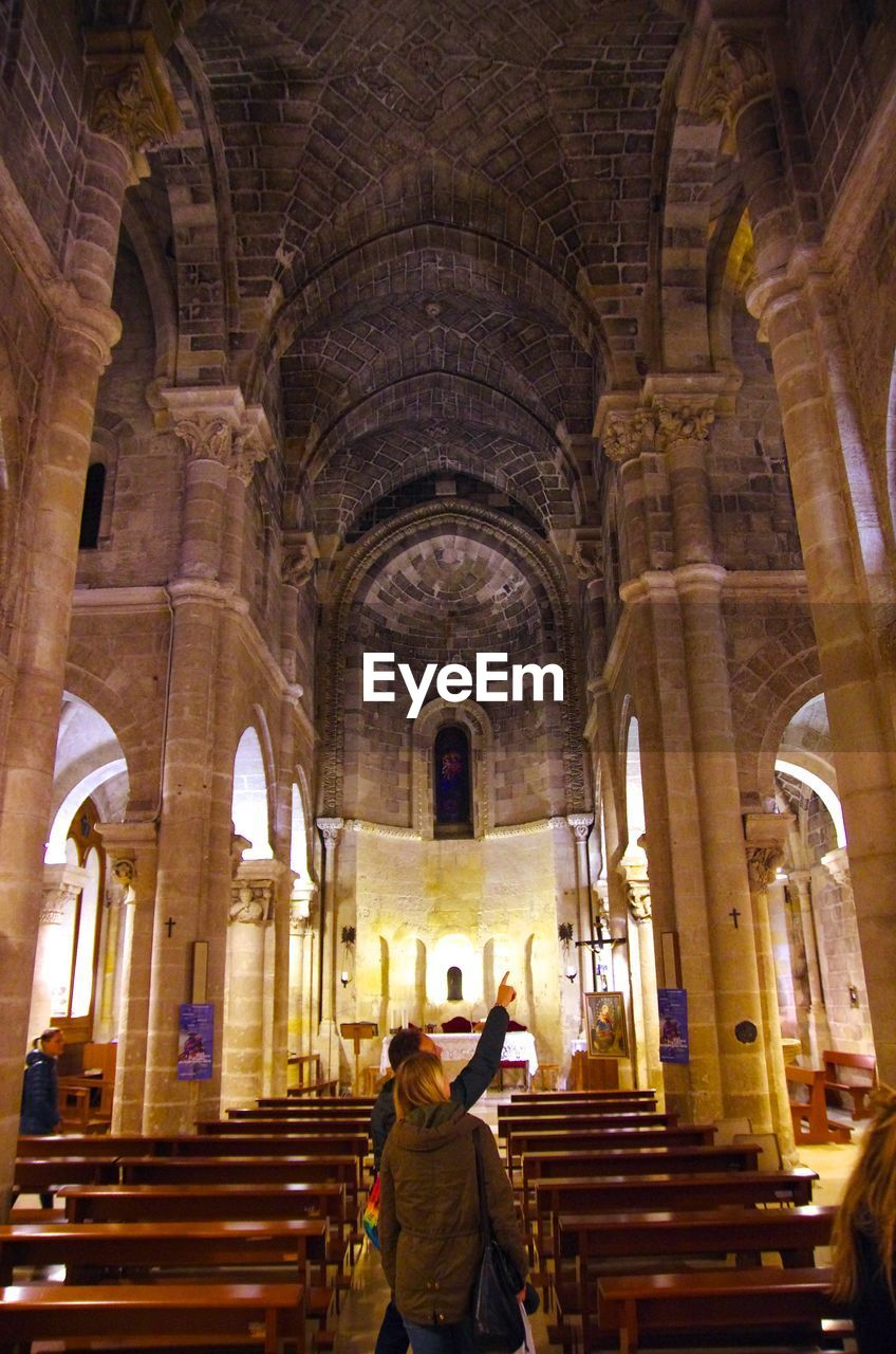 religion, place of worship, spirituality, arch, rear view, architecture, built structure, travel destinations, indoors, real people, standing, pew, women, men, one person, day, adult, adults only, people