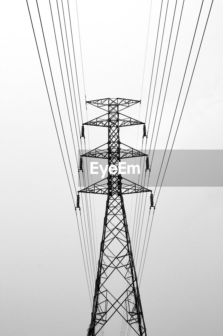 LOW ANGLE VIEW OF CRANES AGAINST ELECTRICITY PYLON