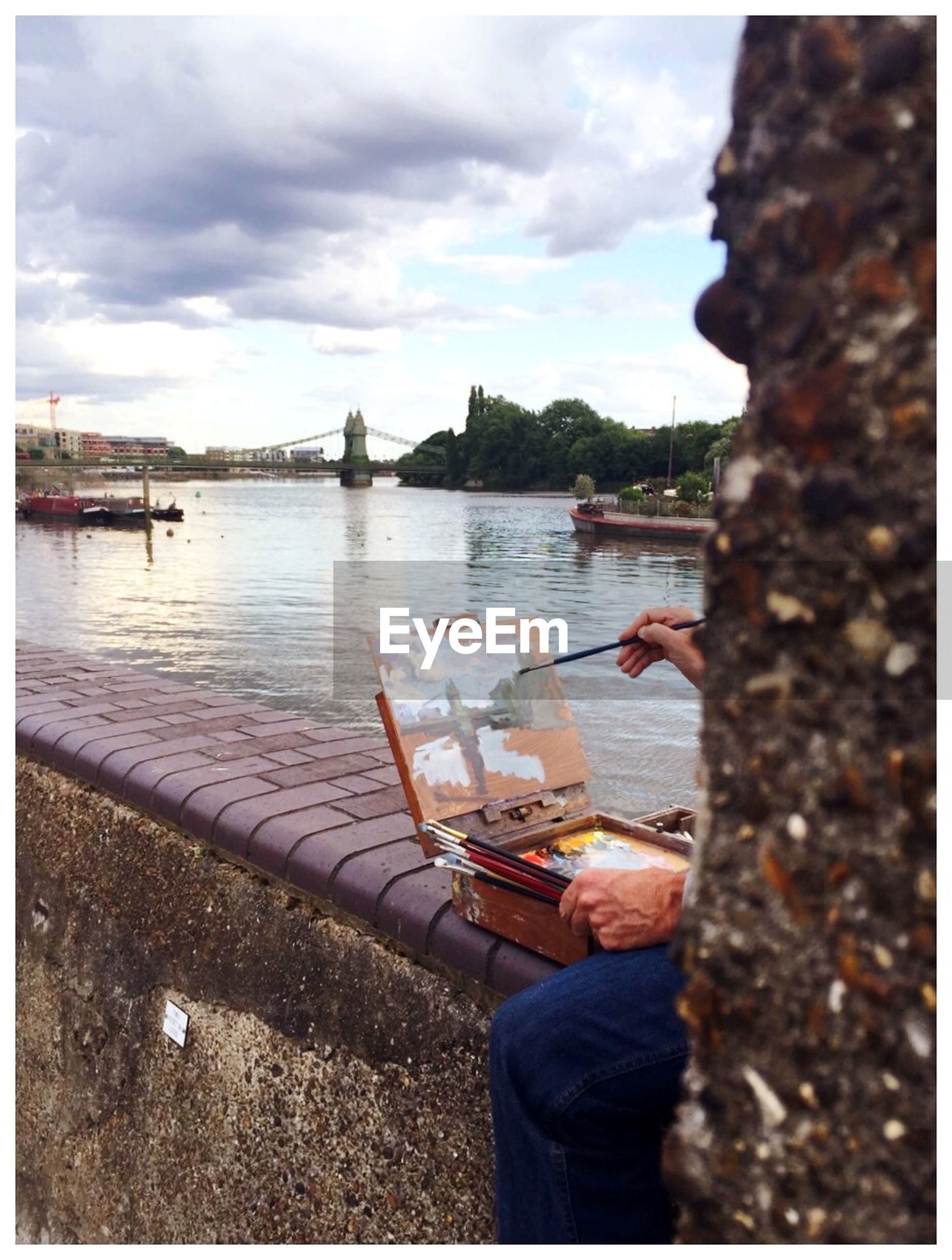 Cropped image of man painting while sitting on retaining wall by river
