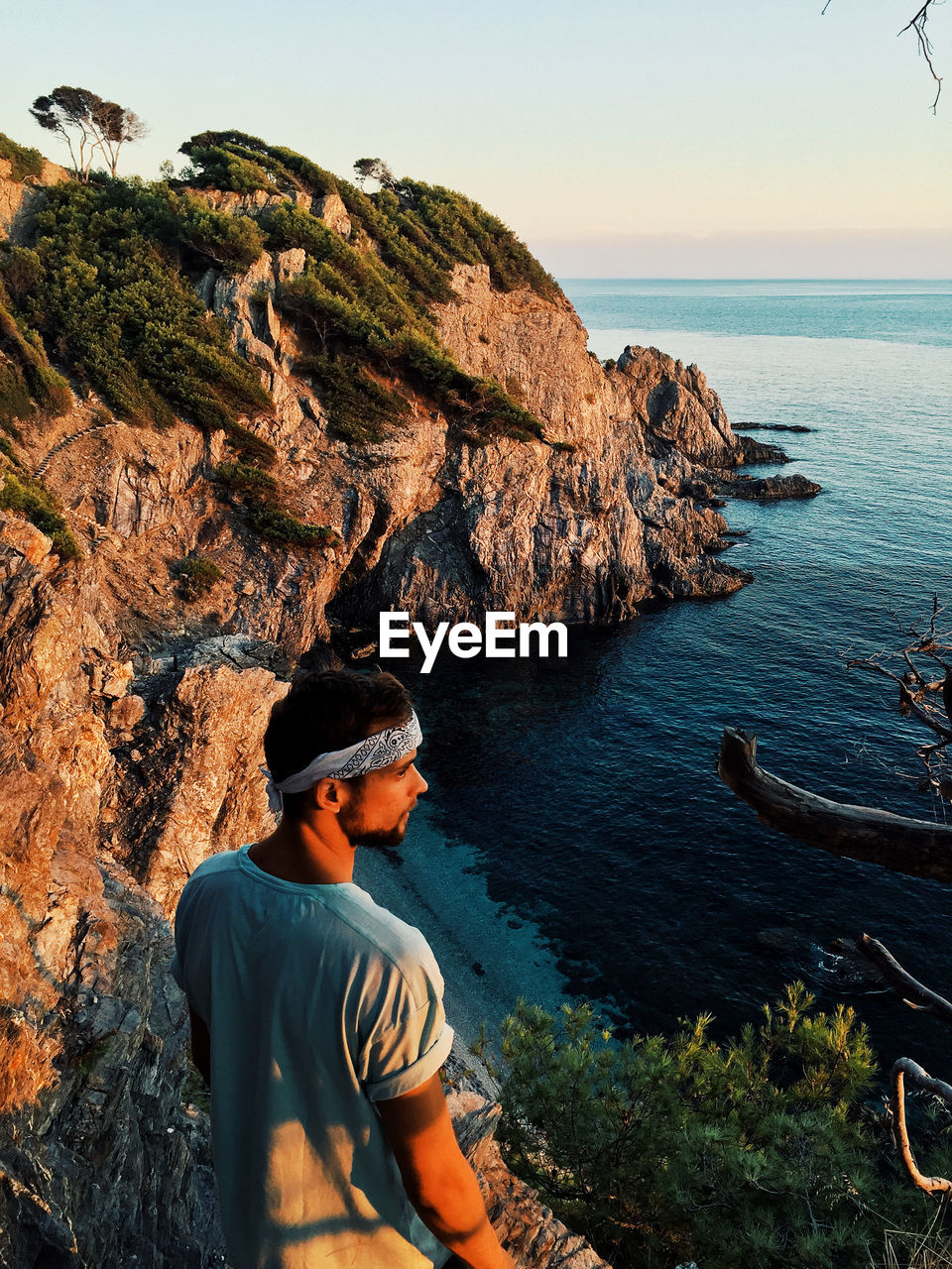water, leisure activity, sea, one person, lifestyles, beauty in nature, real people, scenics - nature, rock, solid, rock - object, sky, nature, men, tranquility, horizon, casual clothing, horizon over water, looking at view, outdoors