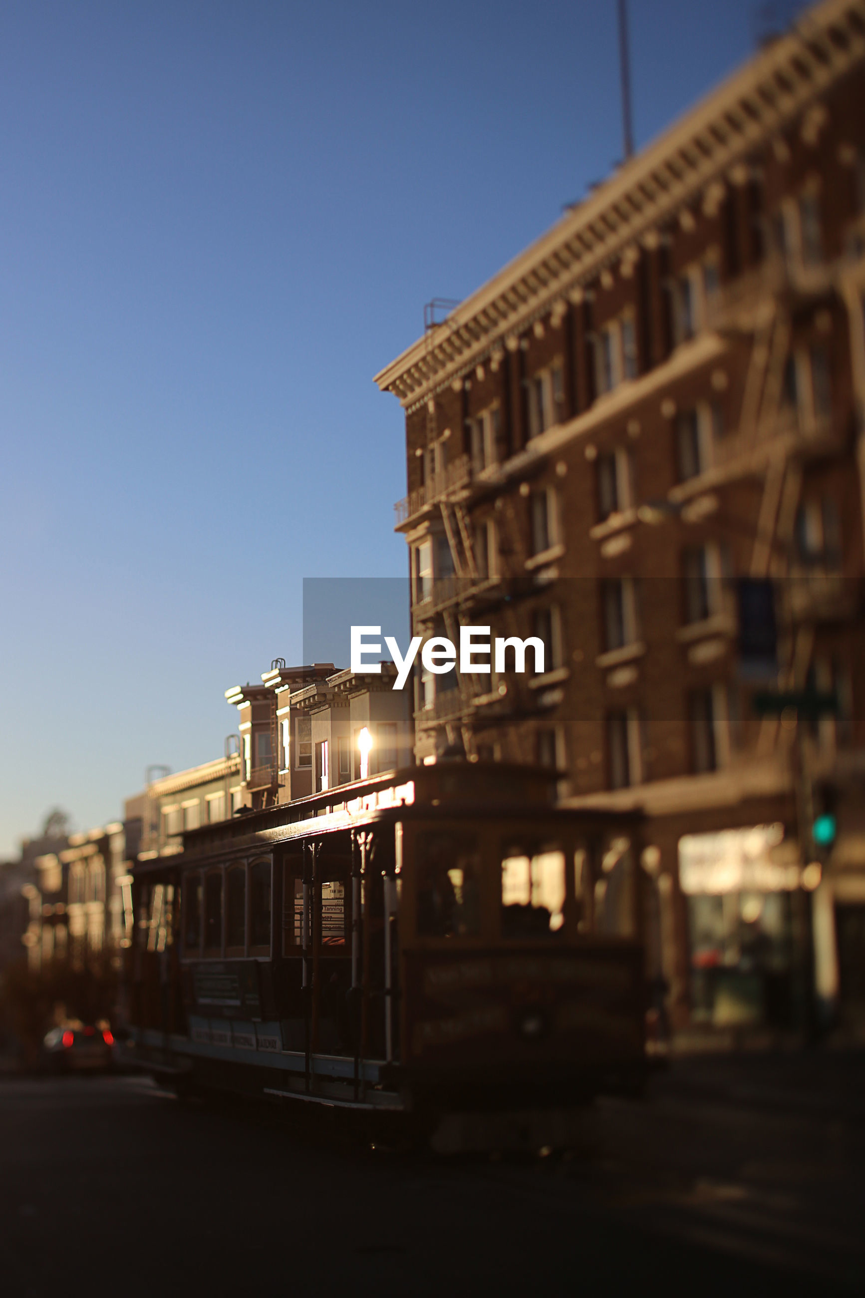 Tilt-shift image of cable car on tramway by building against clear sky