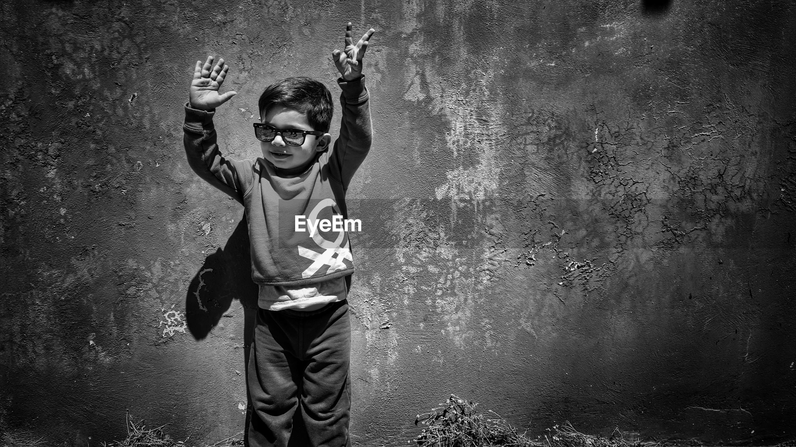 Boy wearing sunglasses while standing against wall