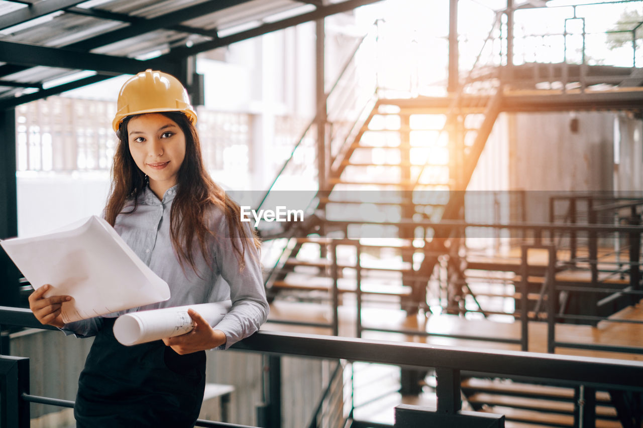 Portrait of female engineer holding blueprints at construction site