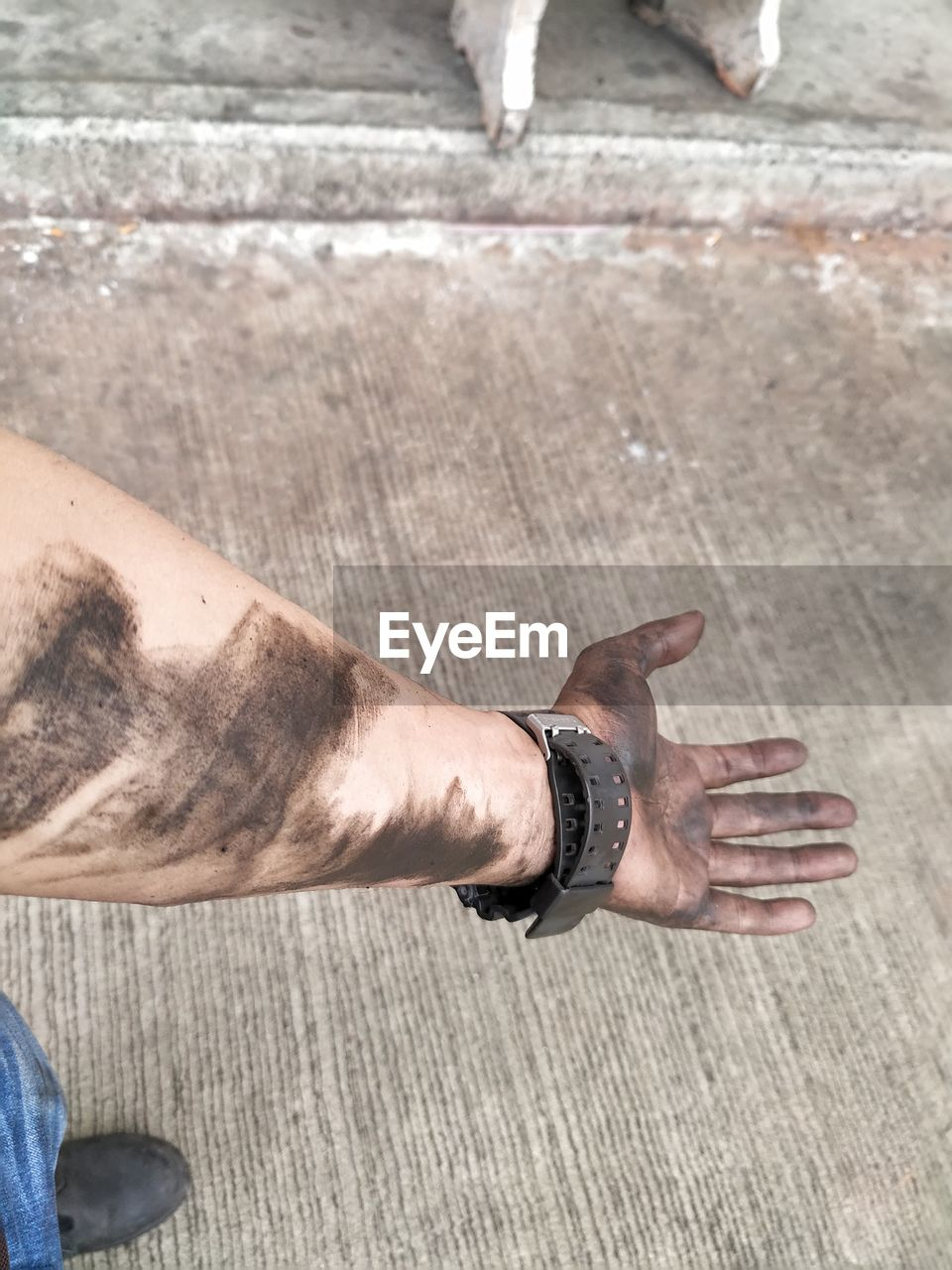 Low section of man showing messy hand while standing in city