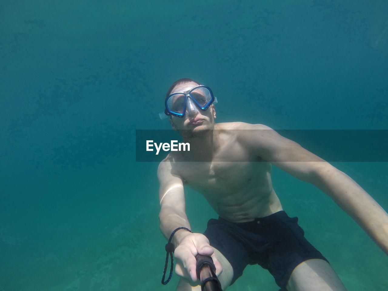 Shirtless man taking selfie in sea