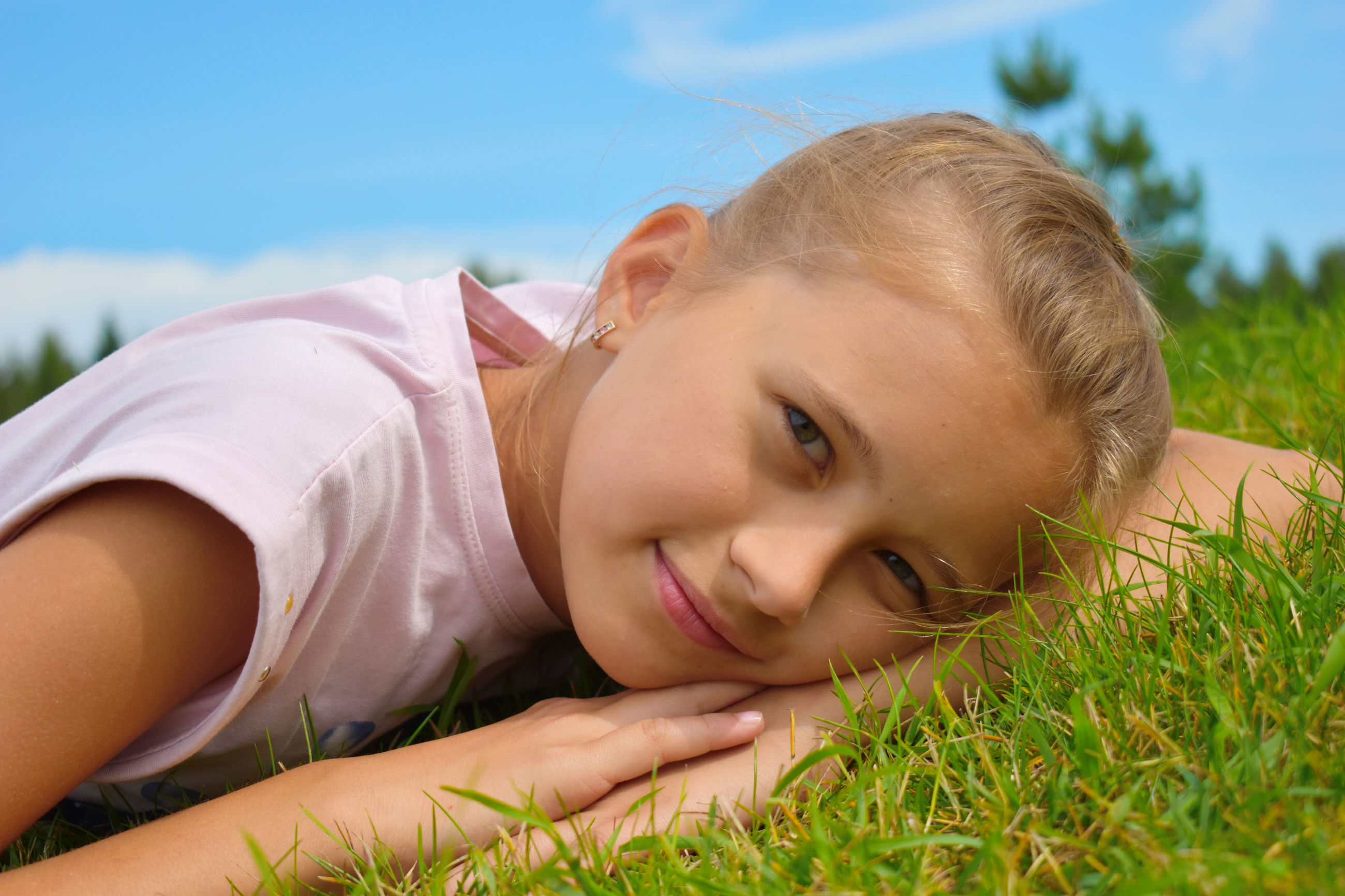 Portrait of girl lying down on grass at park against sky