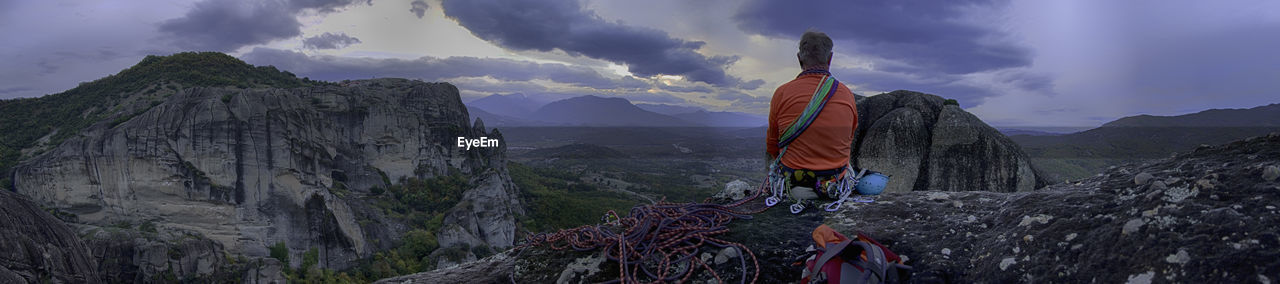 Panoramic view of man sitting on mountain against sky