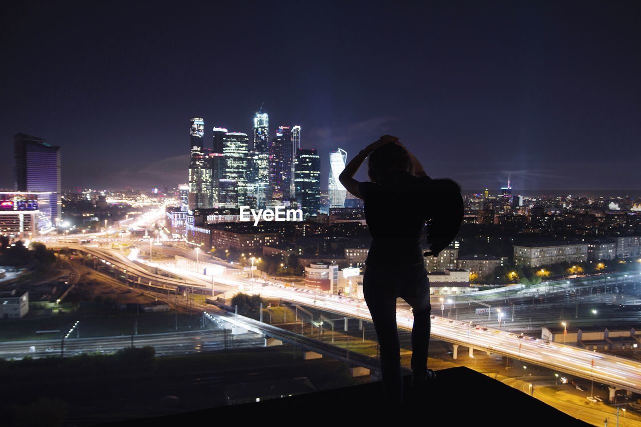 Silhouette woman standing on terrace against illuminated cityscape at night