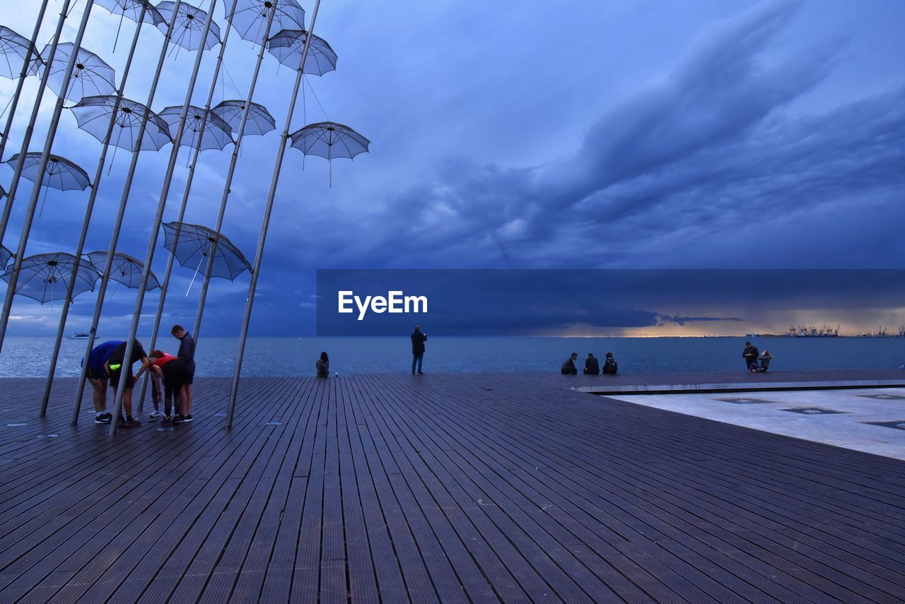 sky, cloud - sky, sea, water, group of people, real people, horizon, scenics - nature, nature, horizon over water, leisure activity, beach, men, lifestyles, dusk, land, sunset, women, people, outdoors