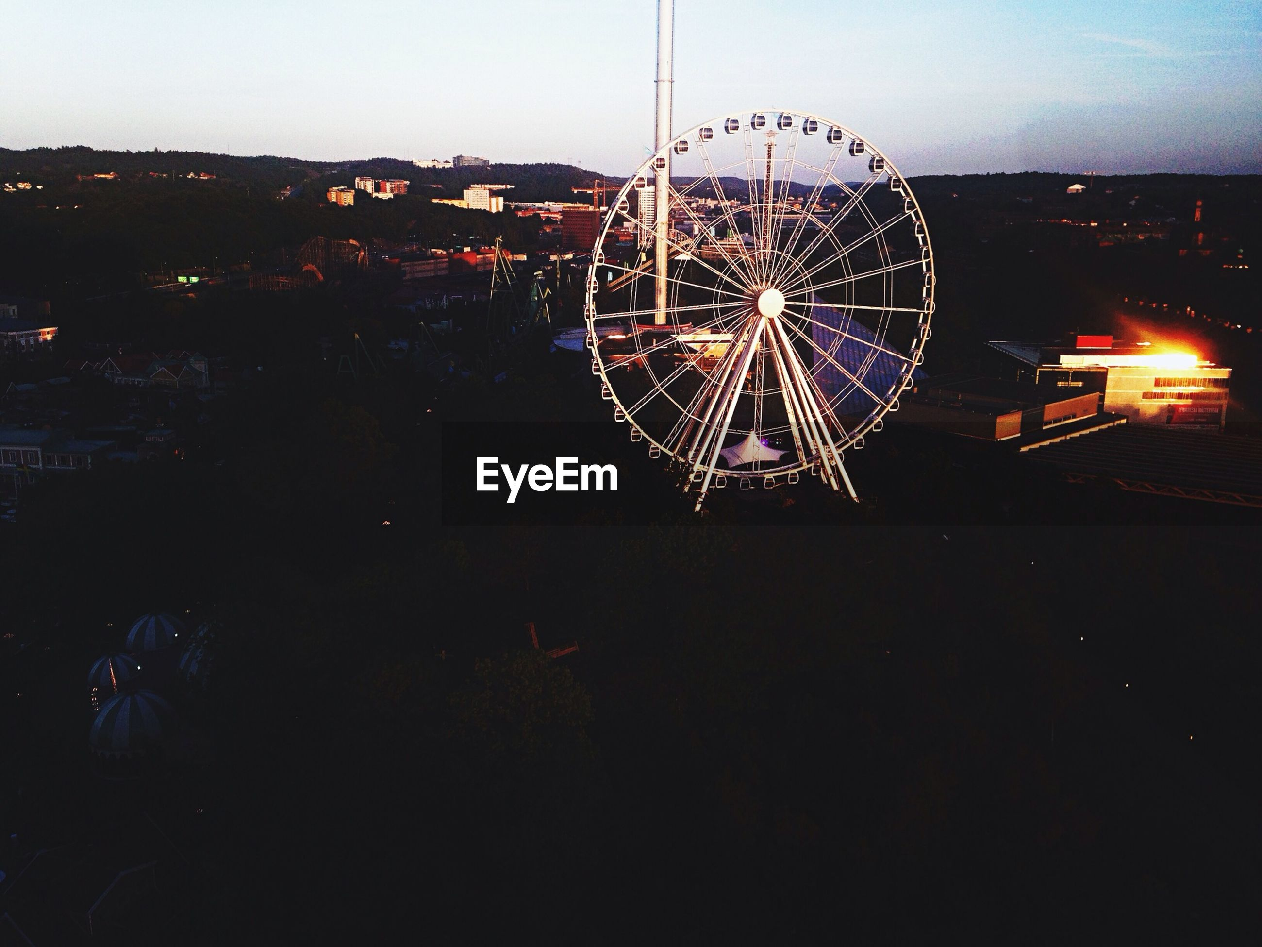 illuminated, night, arts culture and entertainment, ferris wheel, amusement park, amusement park ride, sky, built structure, low angle view, silhouette, outdoors, architecture, dusk, motion, long exposure, clear sky, building exterior, city, incidental people, no people