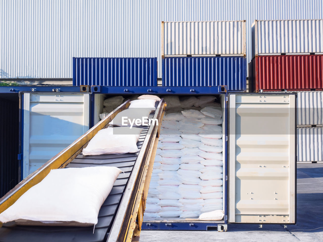 Sacks On Conveyor Belt Against Cargo Containers