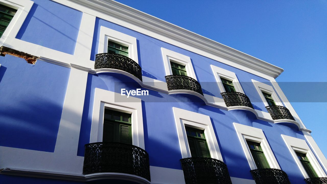 Low Angle View Of Blue Building Against Sky On Sunny Day