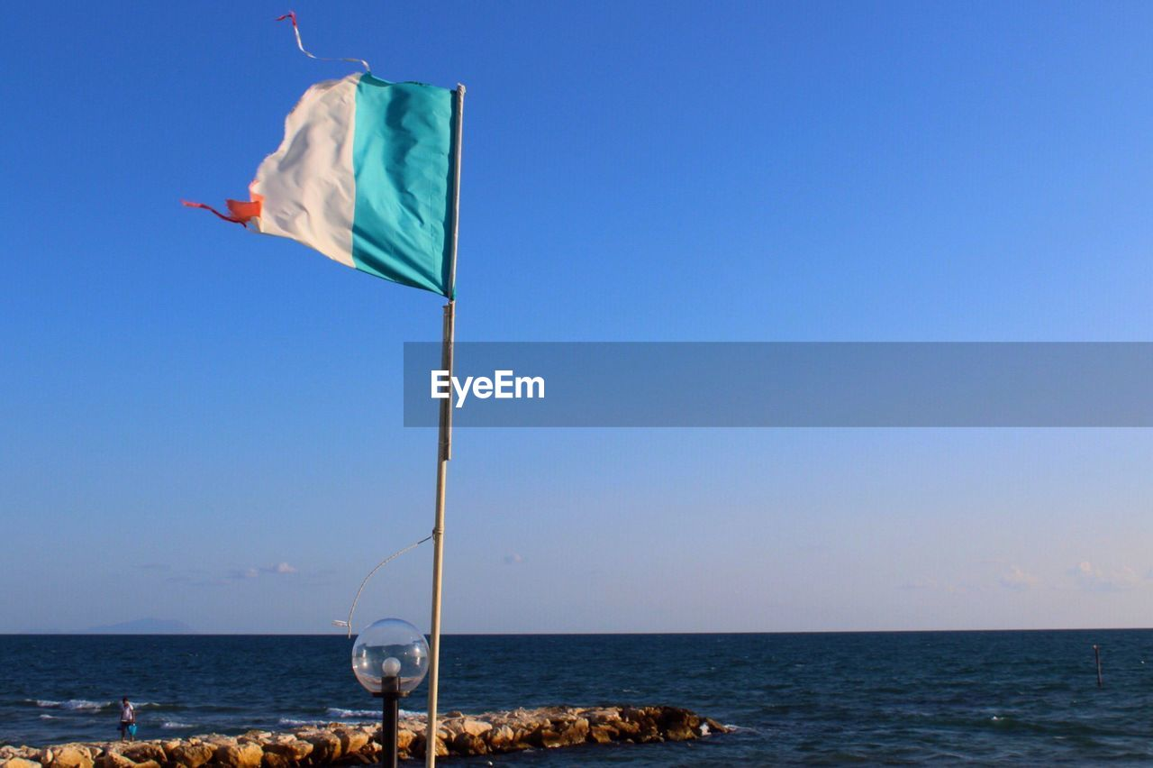 water, sea, sky, flag, horizon over water, horizon, copy space, clear sky, day, patriotism, nature, blue, no people, scenics - nature, wind, beauty in nature, outdoors, environment