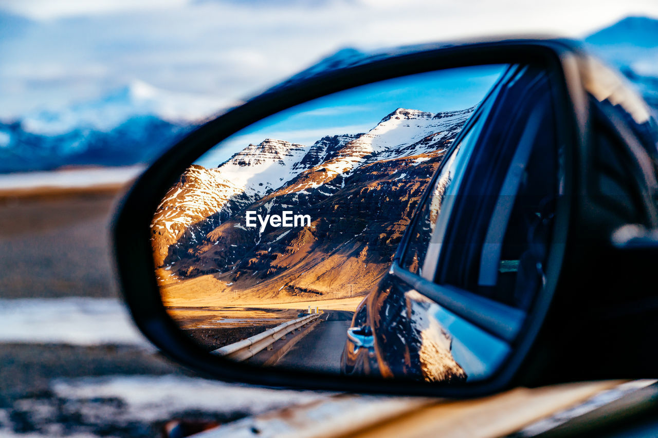 Reflection of mountains on side-view car mirror during winter