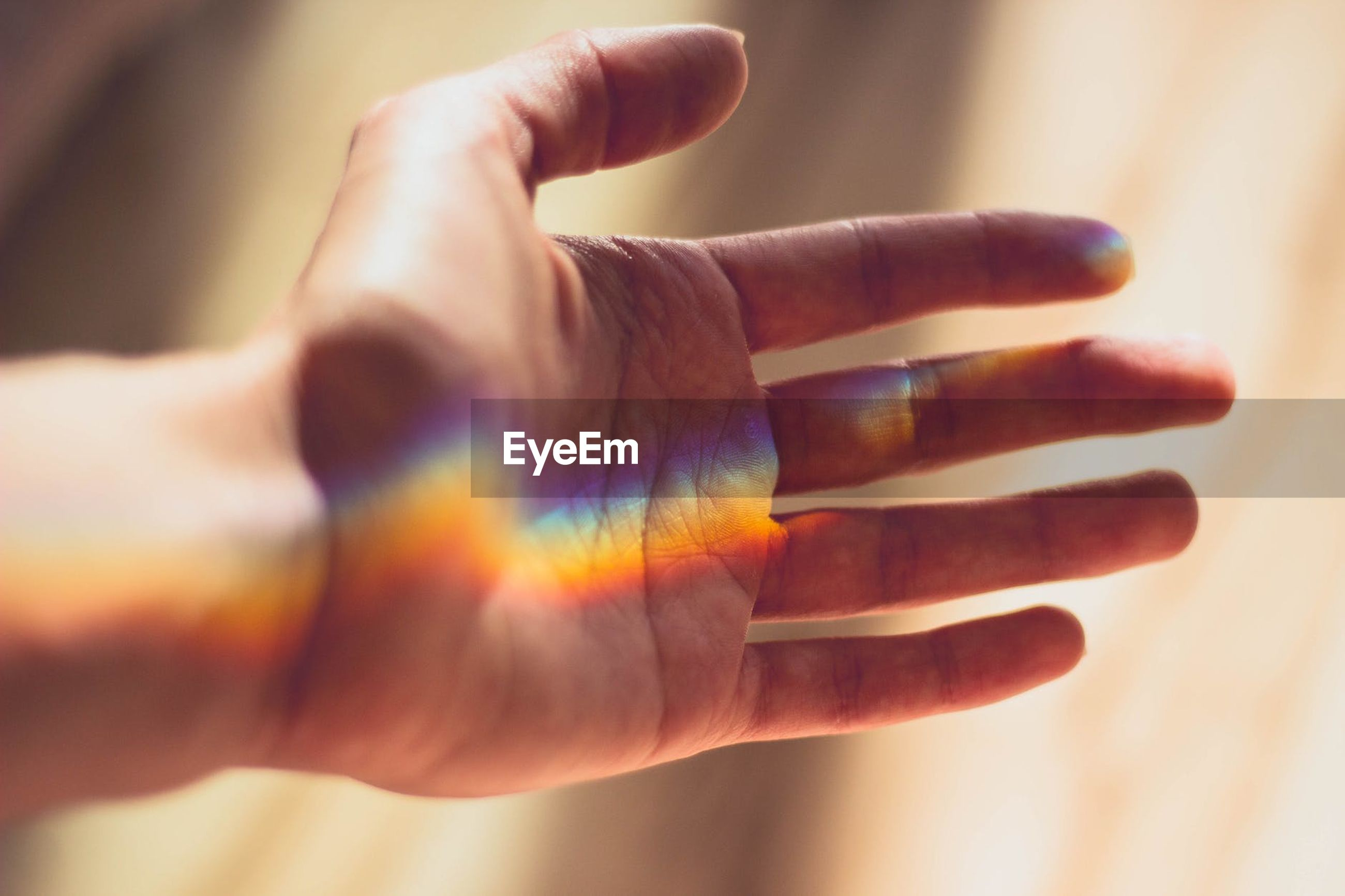 Close-up of colorful sunlight falling on cropped hand