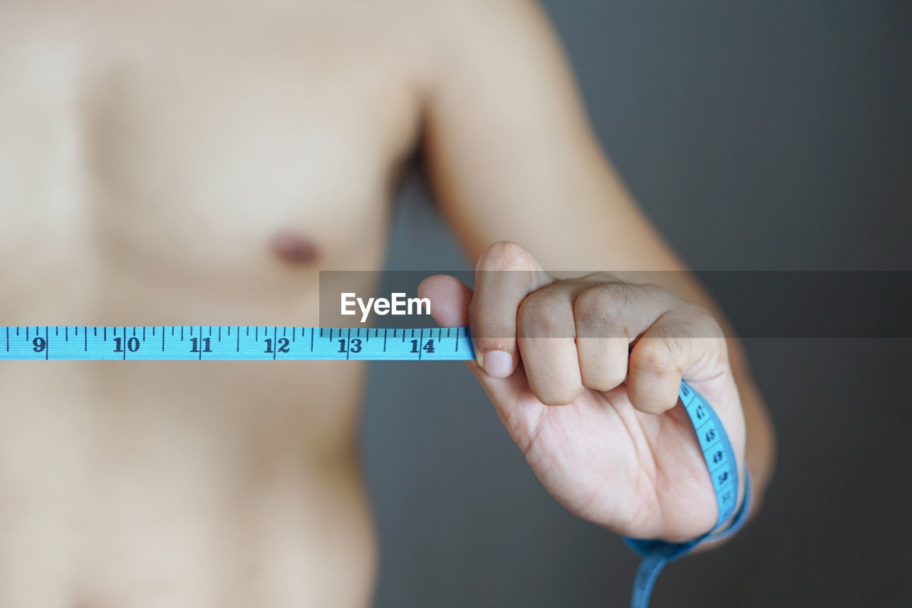 Midsection of shirtless man measuring waist with tape measure